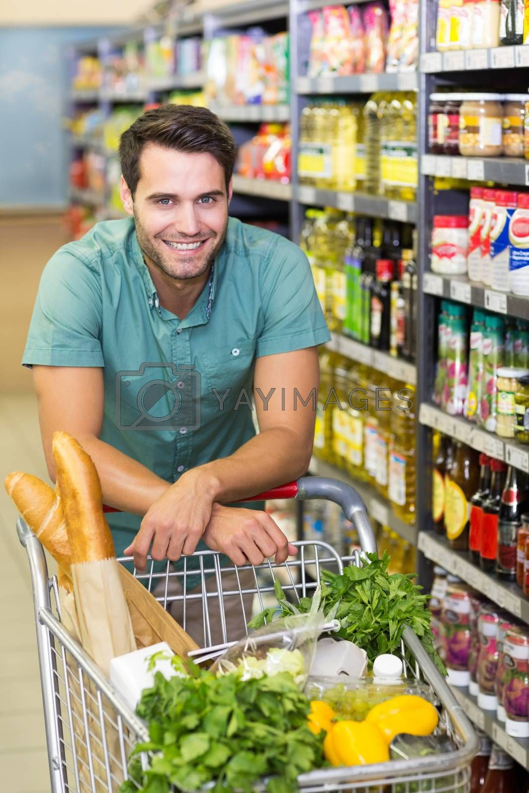 Royalty free image of Portrait of smiling man buy product with his trolley  by Wavebreakmedia
