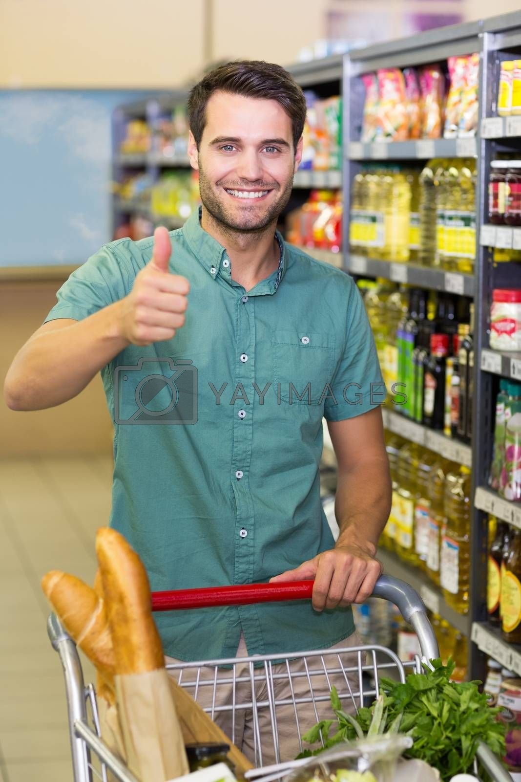 Royalty free image of Portrait of smiling man buy products with his trollet and thumb up  by Wavebreakmedia