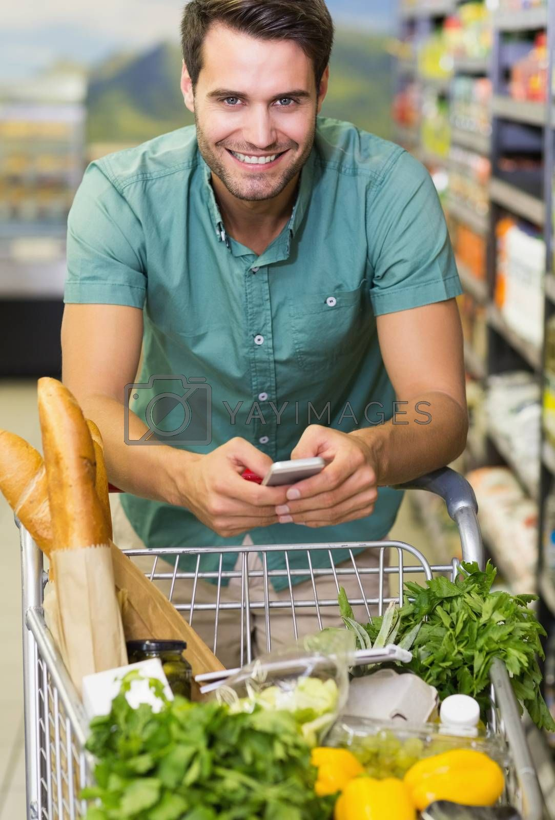 Royalty free image of Portrait of smiling man buy a food and using his smartphone  by Wavebreakmedia