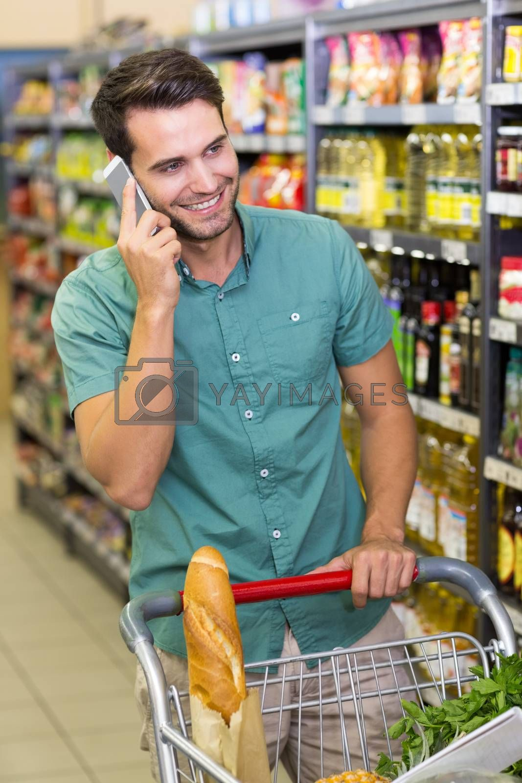 Royalty free image of Smiling man buy food and phoning  by Wavebreakmedia