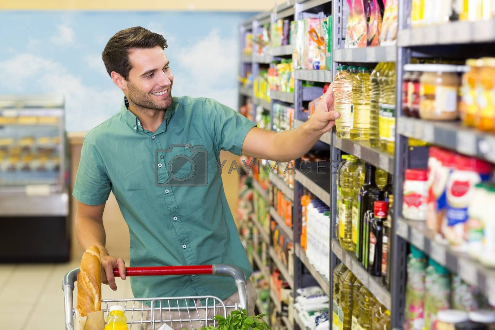 Royalty free image of Smiling man taking a oil in the aisle  by Wavebreakmedia
