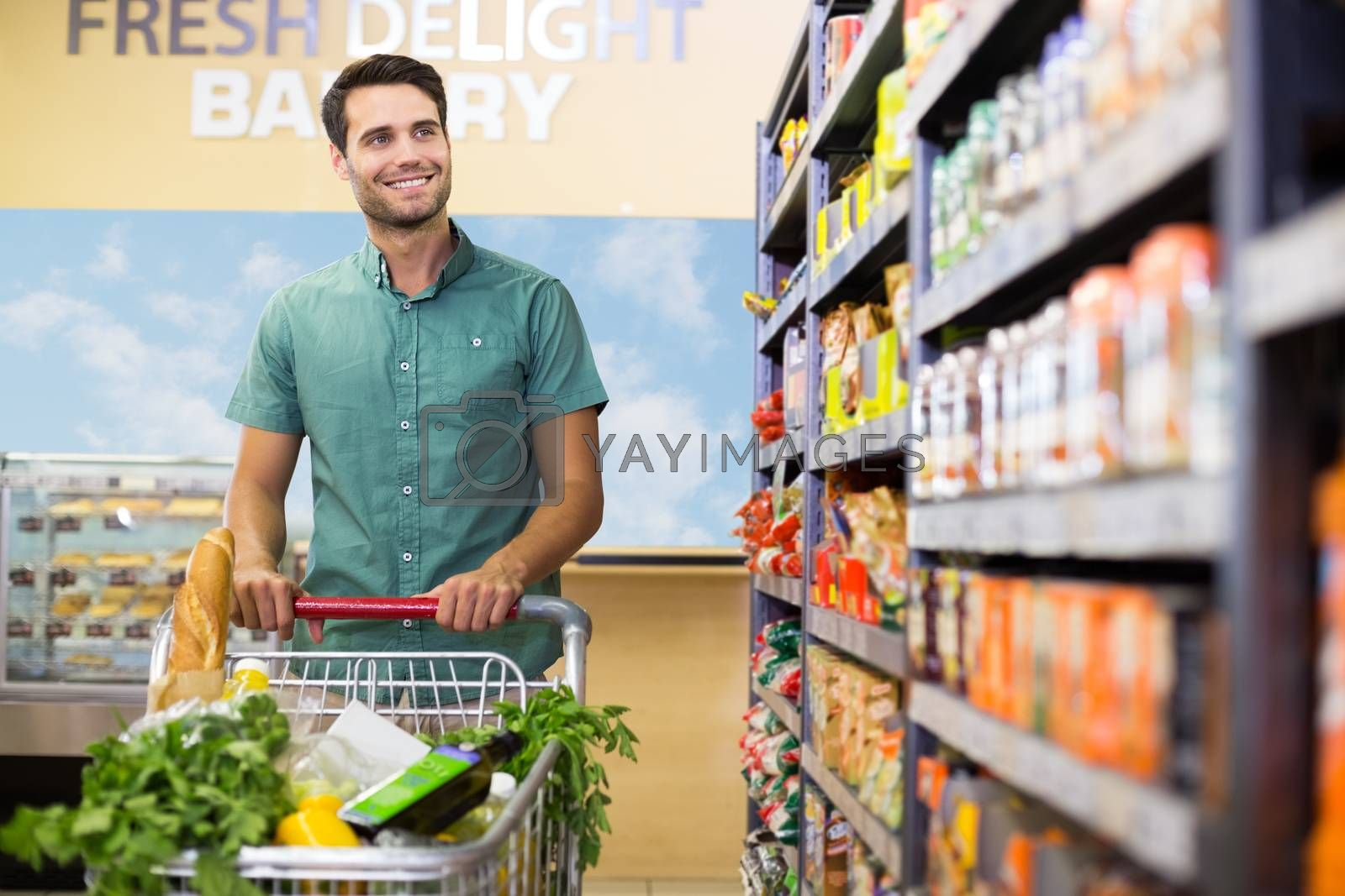 Royalty free image of Portrait of smiling man walking in aisle with his trollet  by Wavebreakmedia