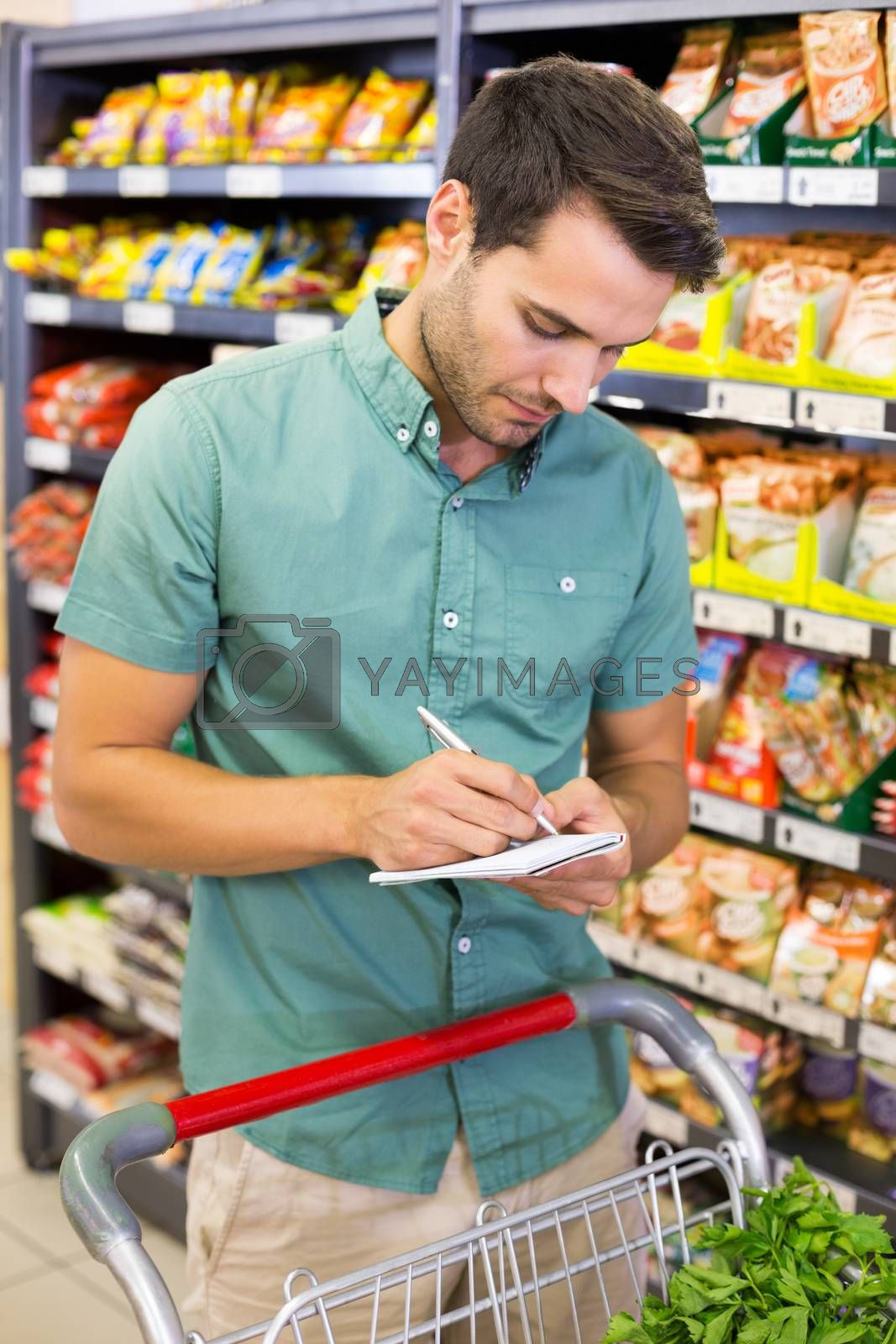 Royalty free image of Serious man writing on list on his notepad  by Wavebreakmedia