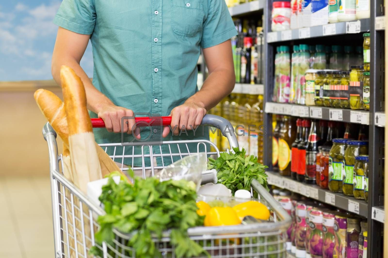 Royalty free image of Man buy products with his trolley  by Wavebreakmedia