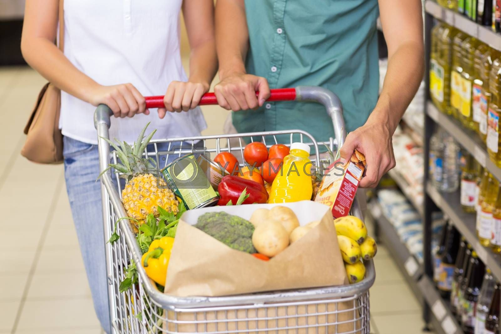 Royalty free image of Bright couple buying food products  by Wavebreakmedia