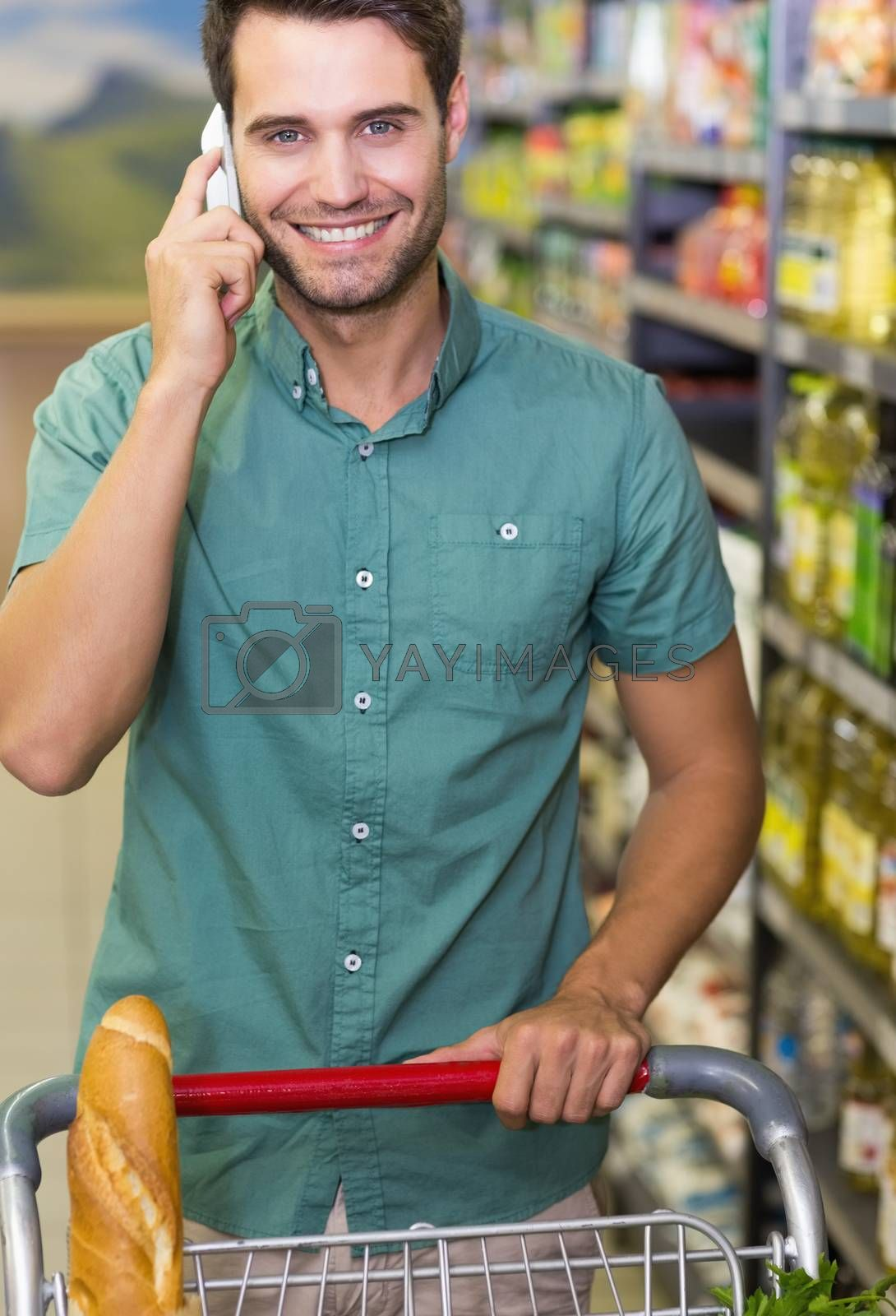 Royalty free image of Portrait of smiling man buy food and phoning  by Wavebreakmedia