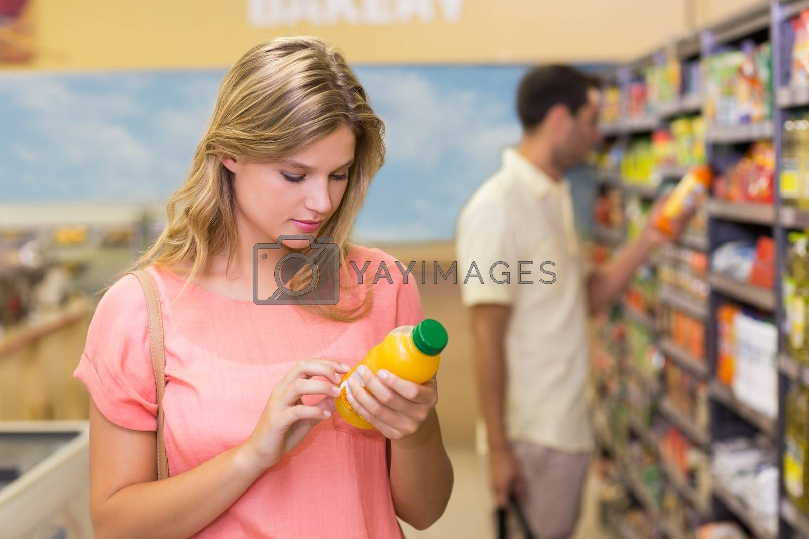 Royalty free image of Pretty blonde woman buying product by Wavebreakmedia