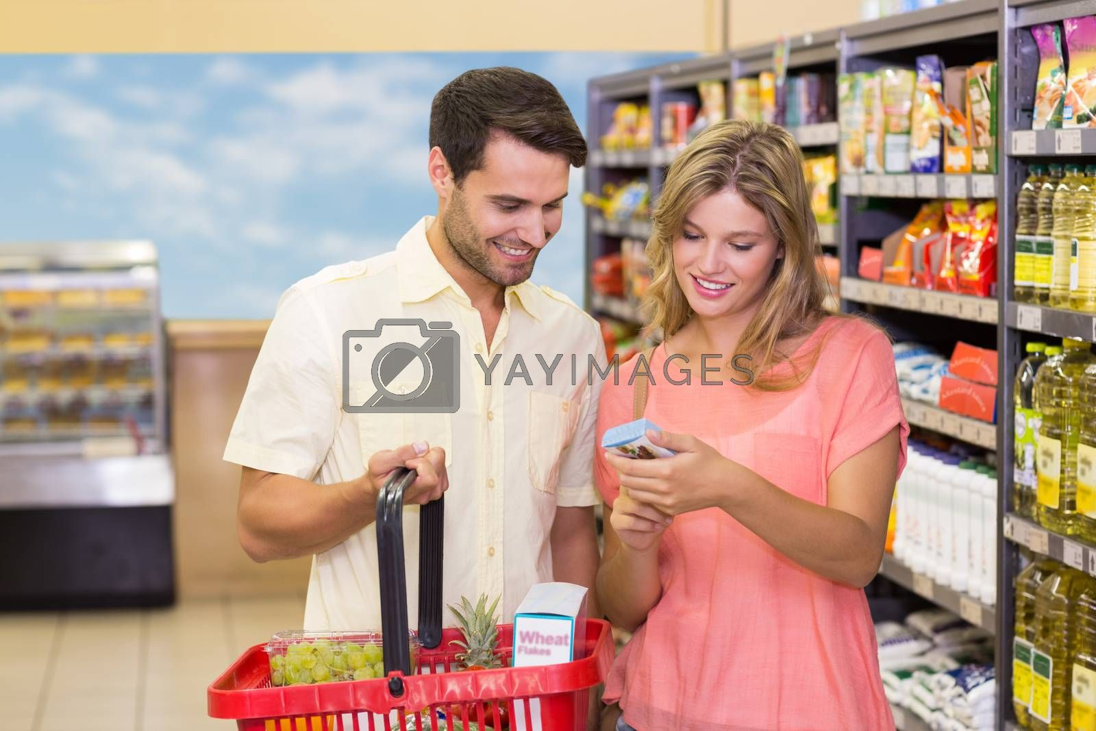 Royalty free image of Smiling bright couple buying food products with shopping basket by Wavebreakmedia