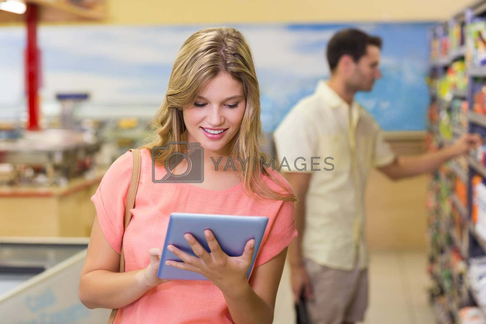 Royalty free image of Smiling pretty blonde woman using digital tablet and buying products  by Wavebreakmedia
