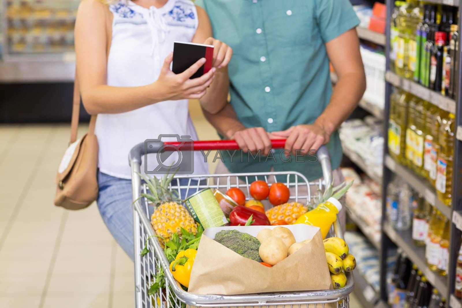 Royalty free image of Smiling bright couple buying food products and using notebook  by Wavebreakmedia