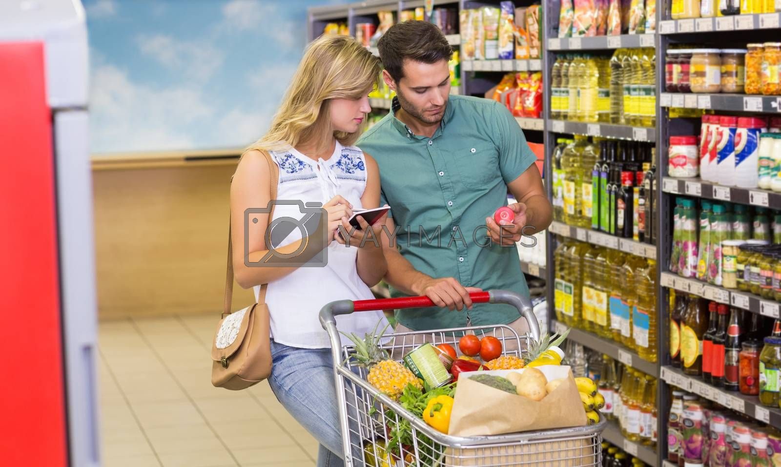 Royalty free image of Bright couple buying food porducts and using notebook  by Wavebreakmedia