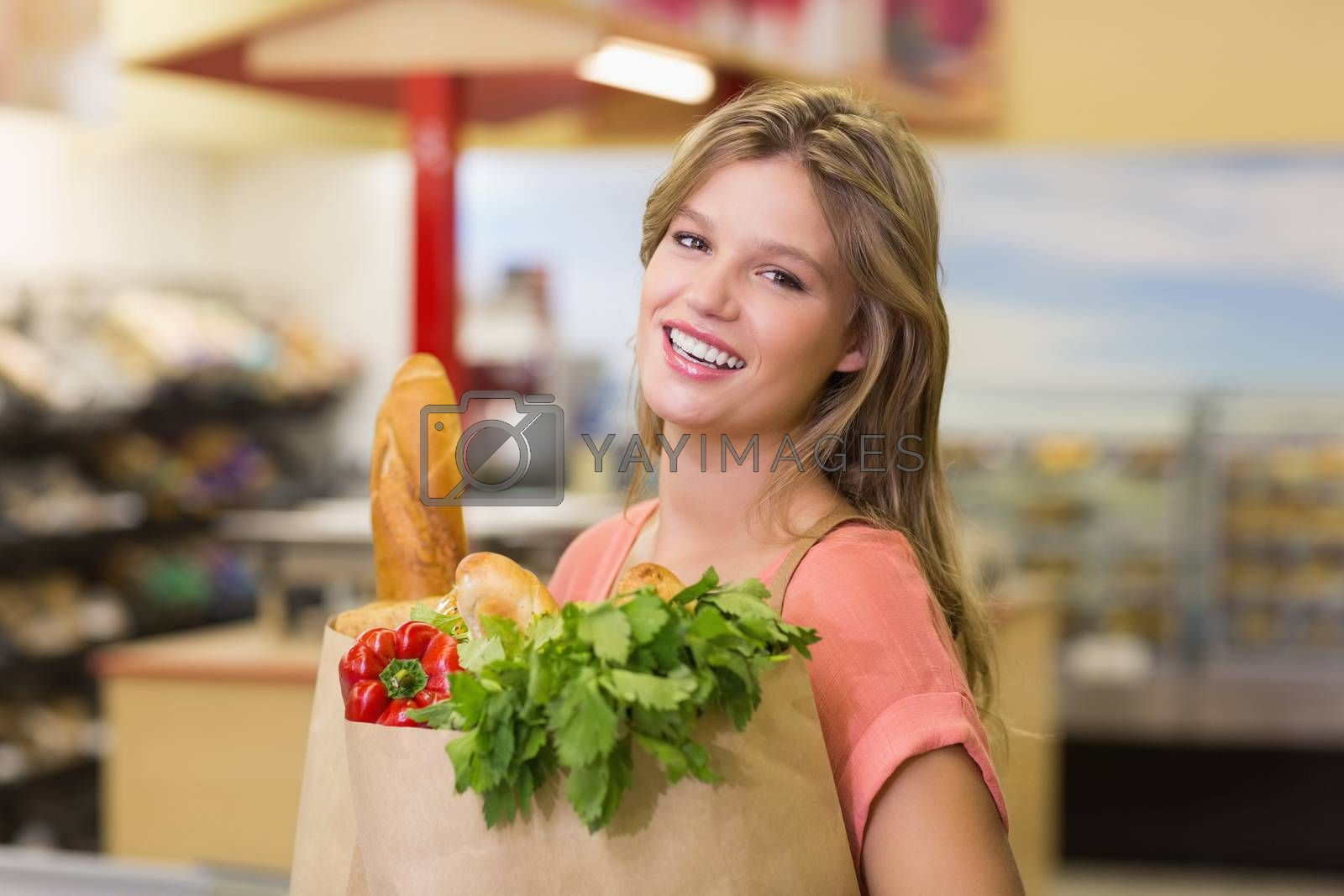 Royalty free image of Portrait of pretty smiling blonde woman buying food products  by Wavebreakmedia