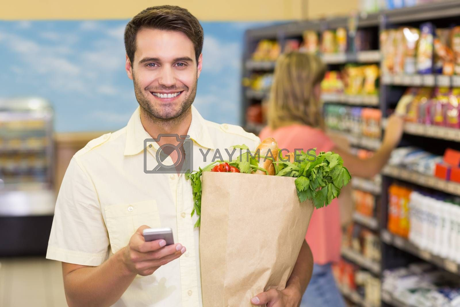 Royalty free image of Portrait of smiling handsome man buying food products and using his smartphone  by Wavebreakmedia