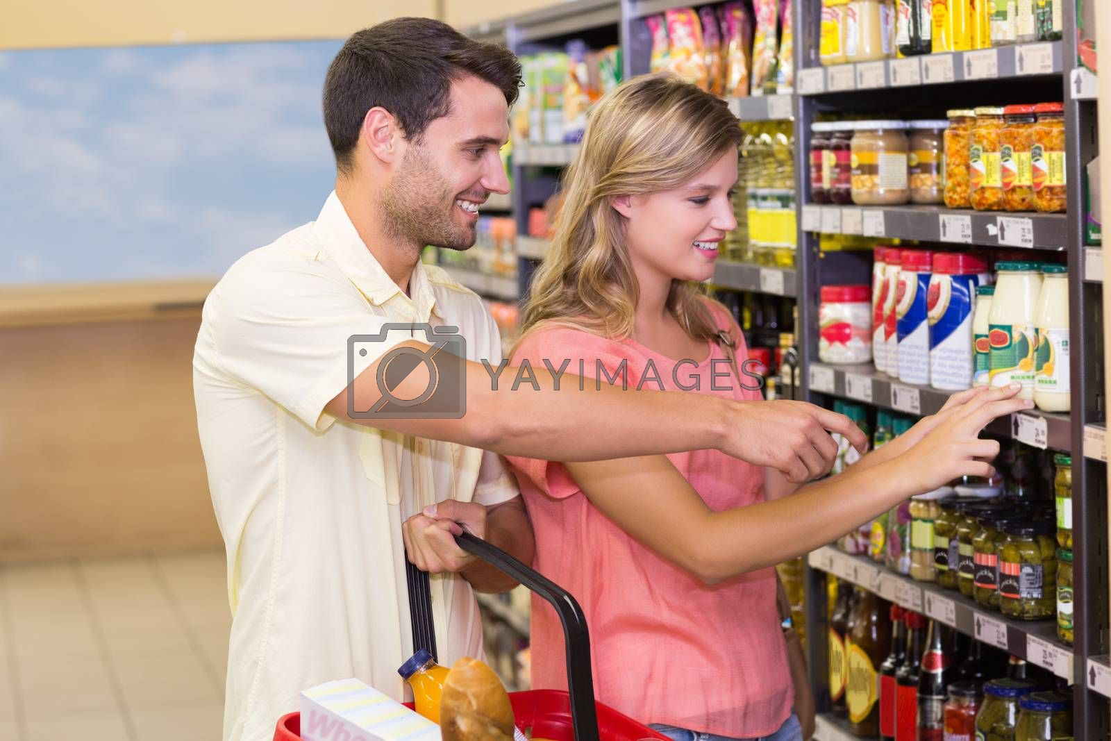 Royalty free image of Smiling bright couple buying food products showing shelf by Wavebreakmedia