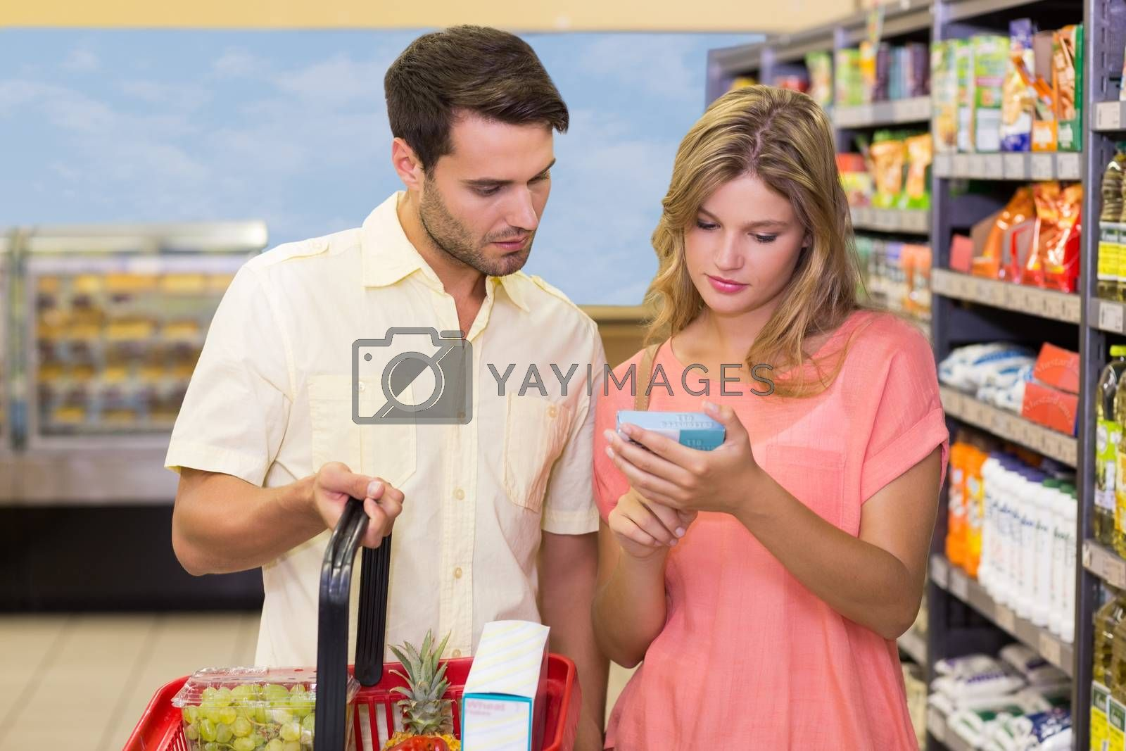 Royalty free image of A bright couple buying products using shopping basket  by Wavebreakmedia