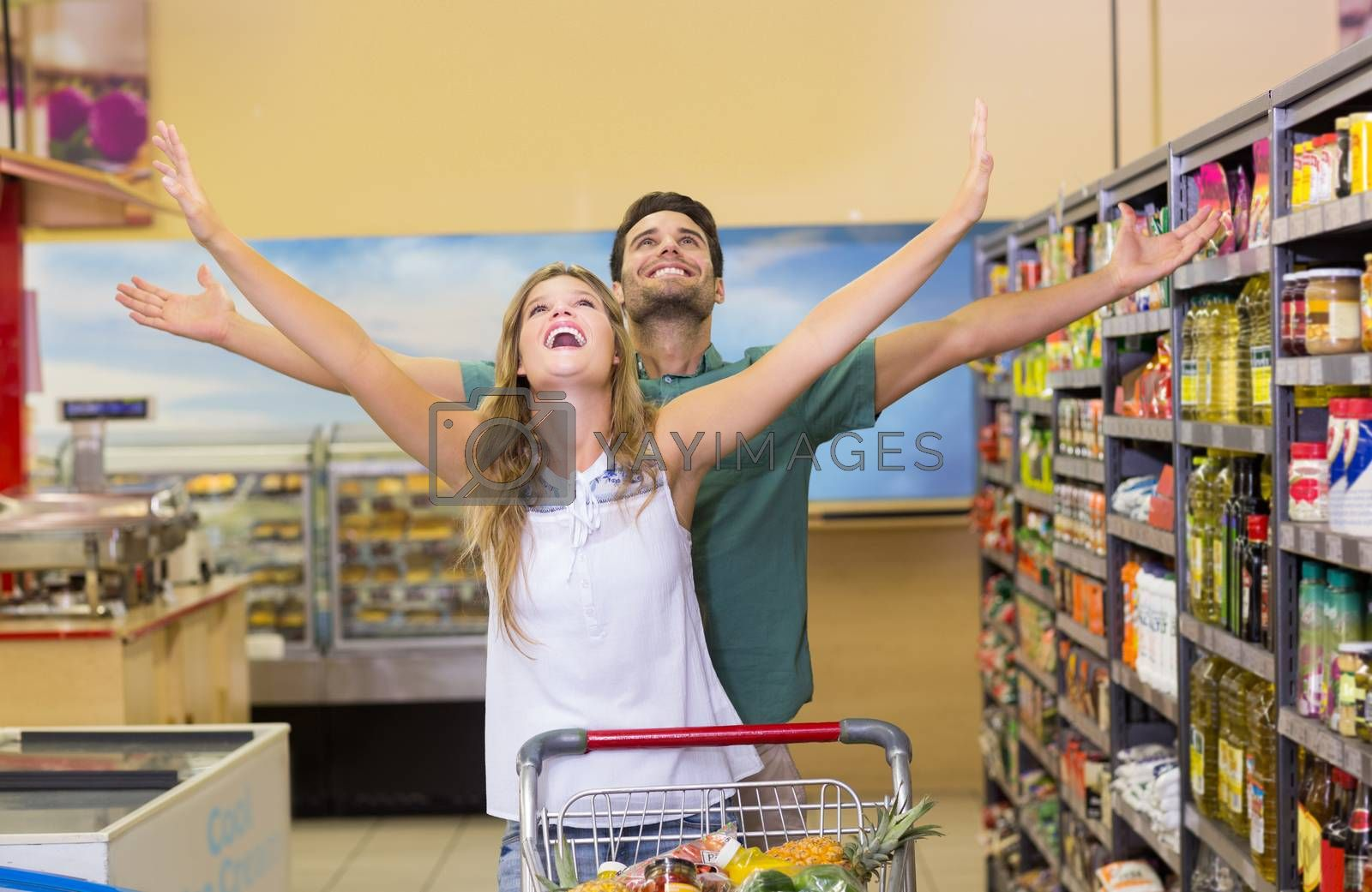 Royalty free image of Happy bright couple buying food products  by Wavebreakmedia