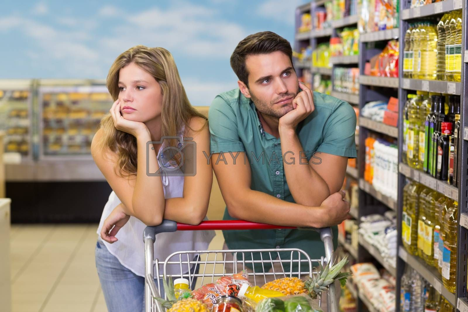 Royalty free image of Serious brght couple buying food products  by Wavebreakmedia