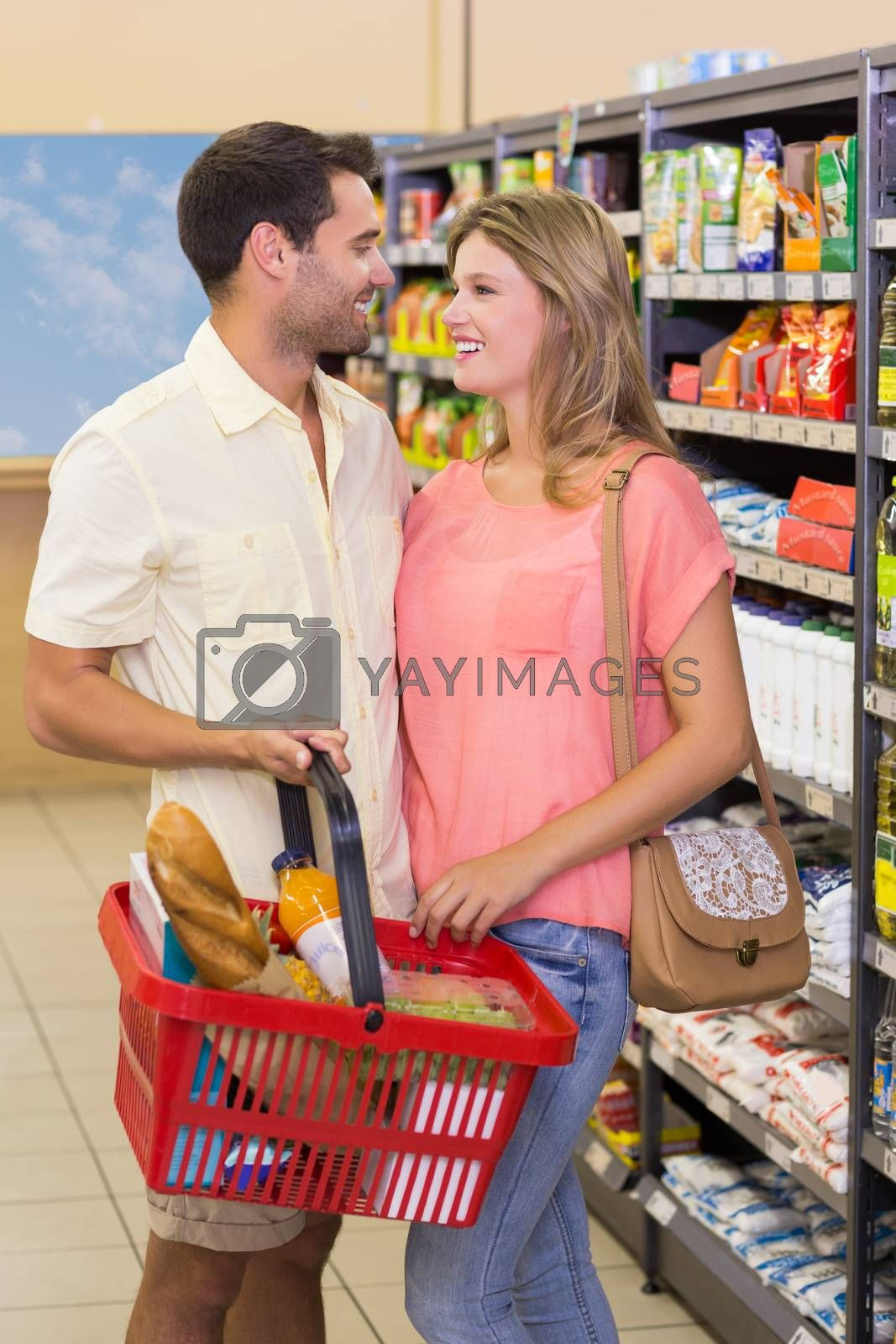Royalty free image of Smiling bright couple buying food products using shopping basket  by Wavebreakmedia