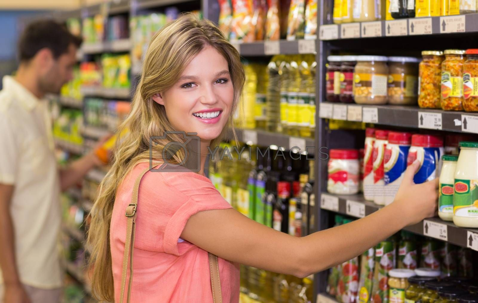 Royalty free image of Portrait of a pretty blonde woman buying food products  by Wavebreakmedia