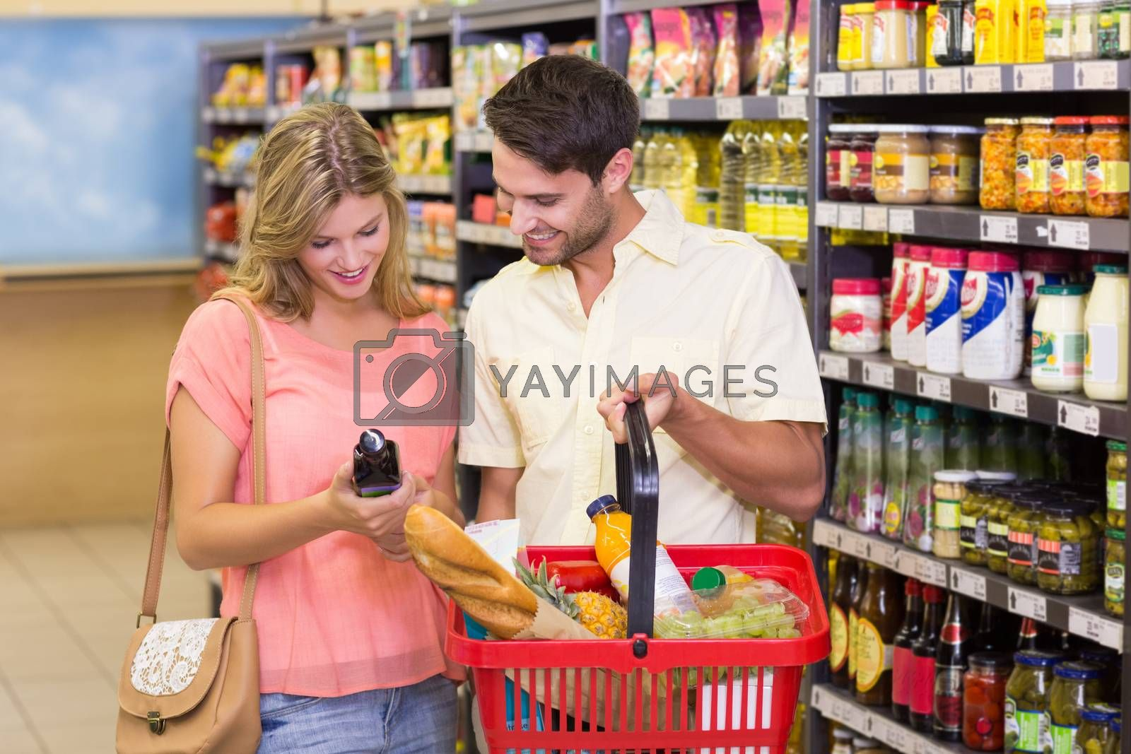 Royalty free image of Smiling bright couple buying food porducts with shopping basket  by Wavebreakmedia