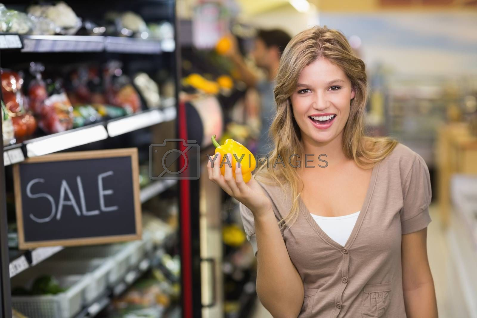 Royalty free image of Portrait of a pretty smiling blonde woman buying vegetables by Wavebreakmedia