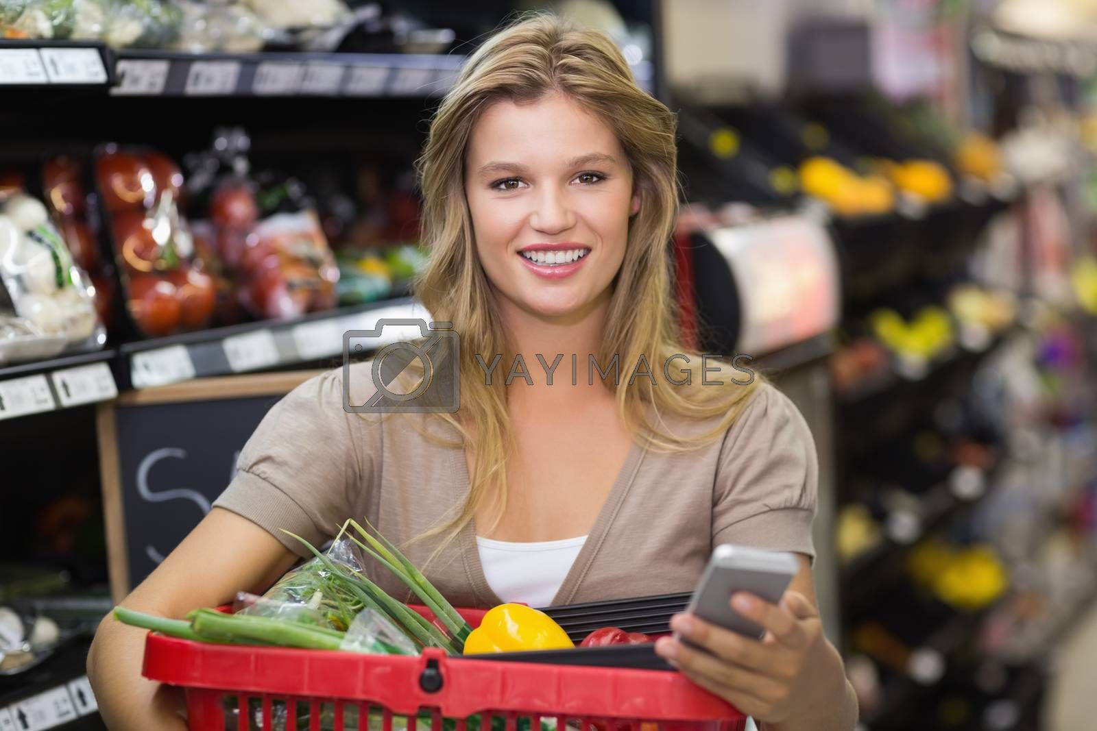 Royalty free image of Portrait of smiling blonde woman buying vegetables and using her smartphone  by Wavebreakmedia