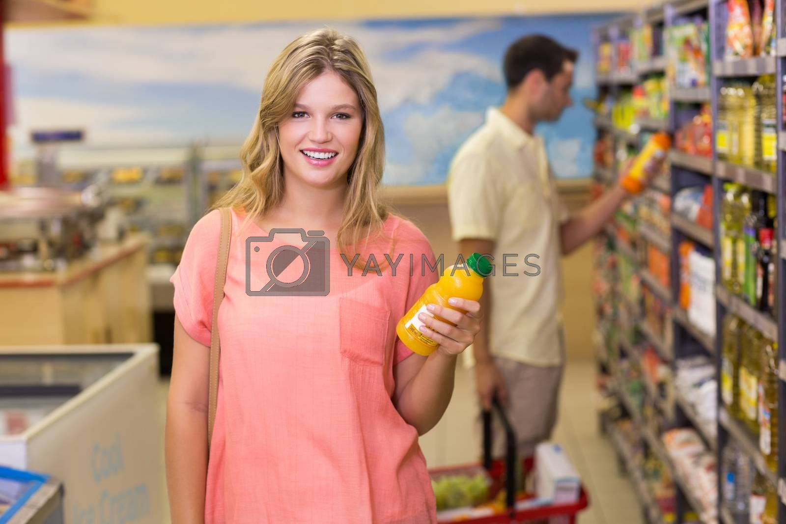Royalty free image of Portrait of a pretty smiling blonde woman buying product  by Wavebreakmedia