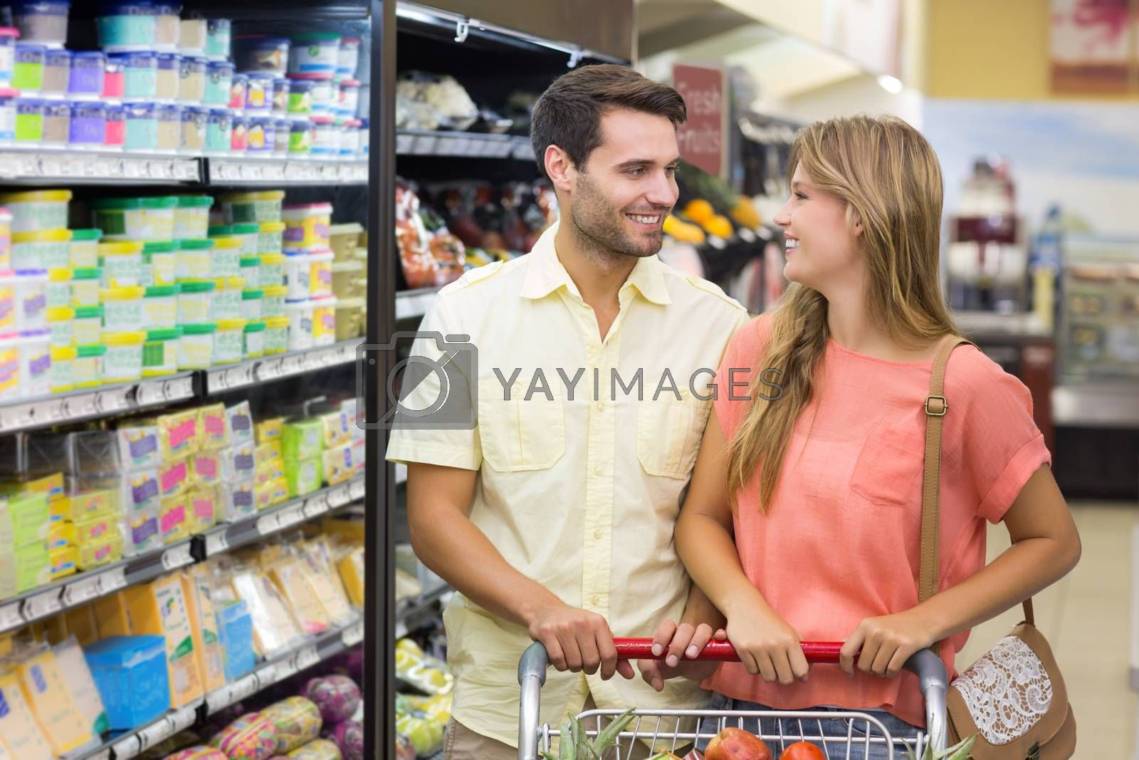 Royalty free image of Smiling bright couple buying products by Wavebreakmedia