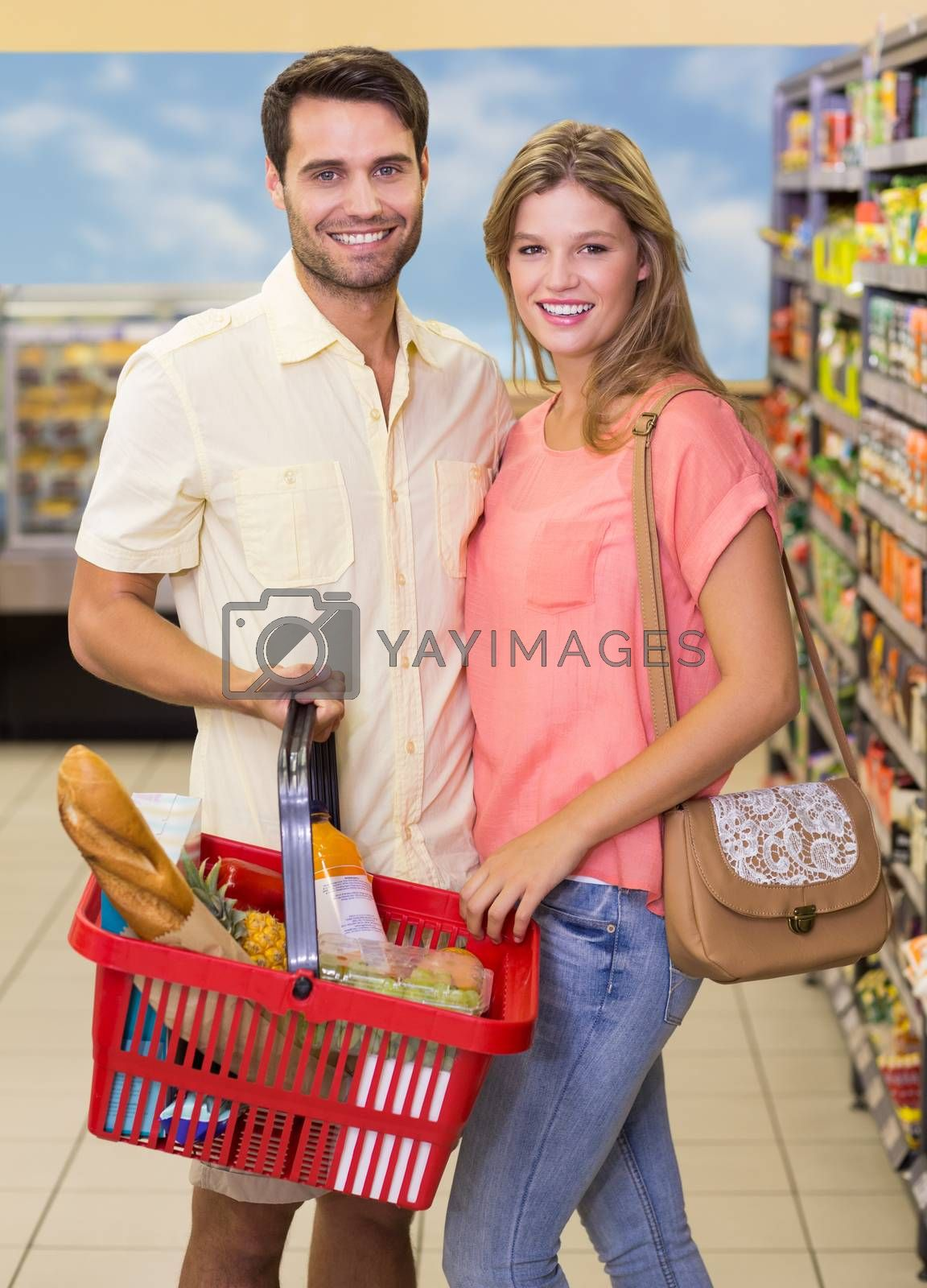 Royalty free image of Portrait of smiling bright couple buying food products using shopping basket by Wavebreakmedia