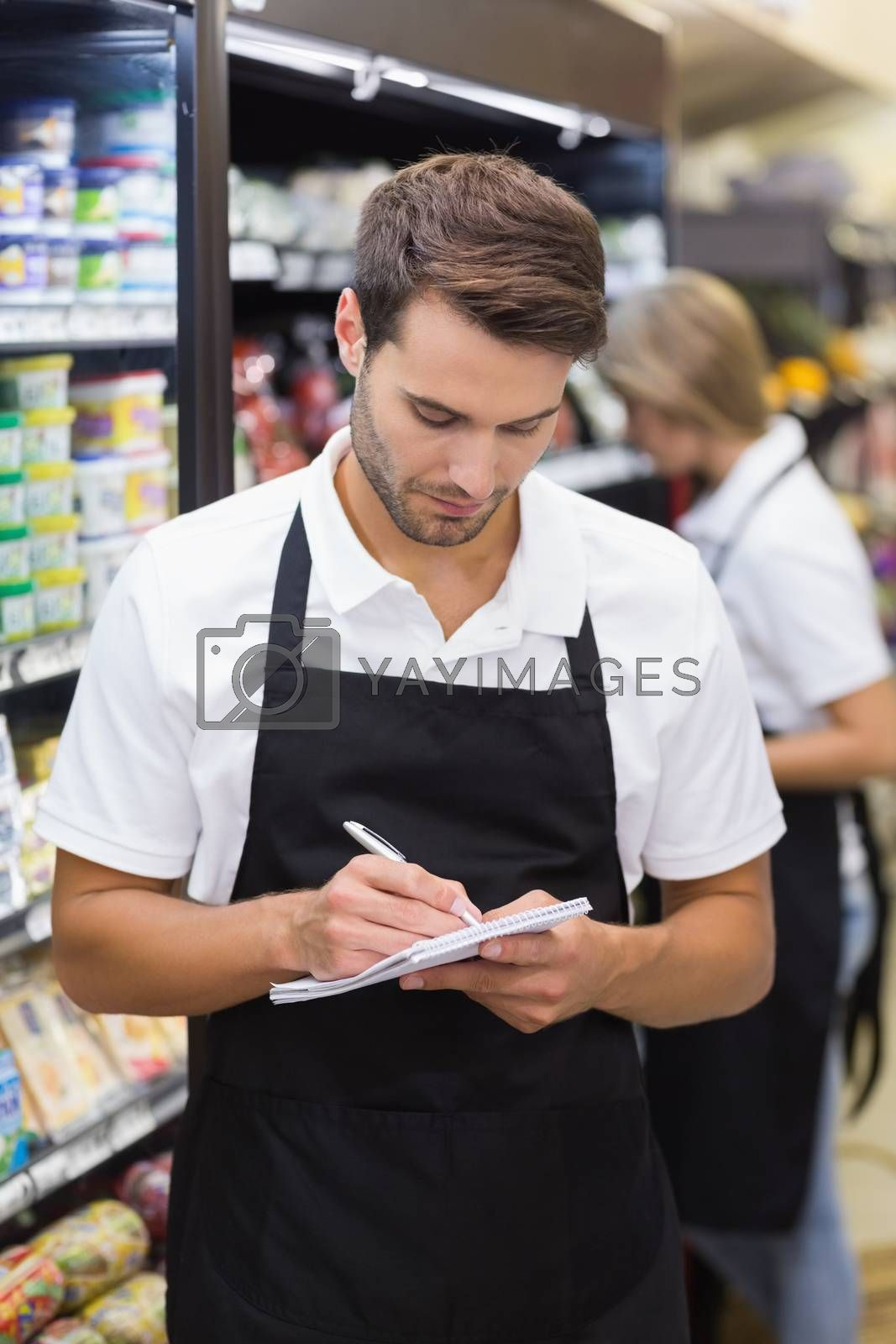 Royalty free image of A serious staff man writing on notepad by Wavebreakmedia