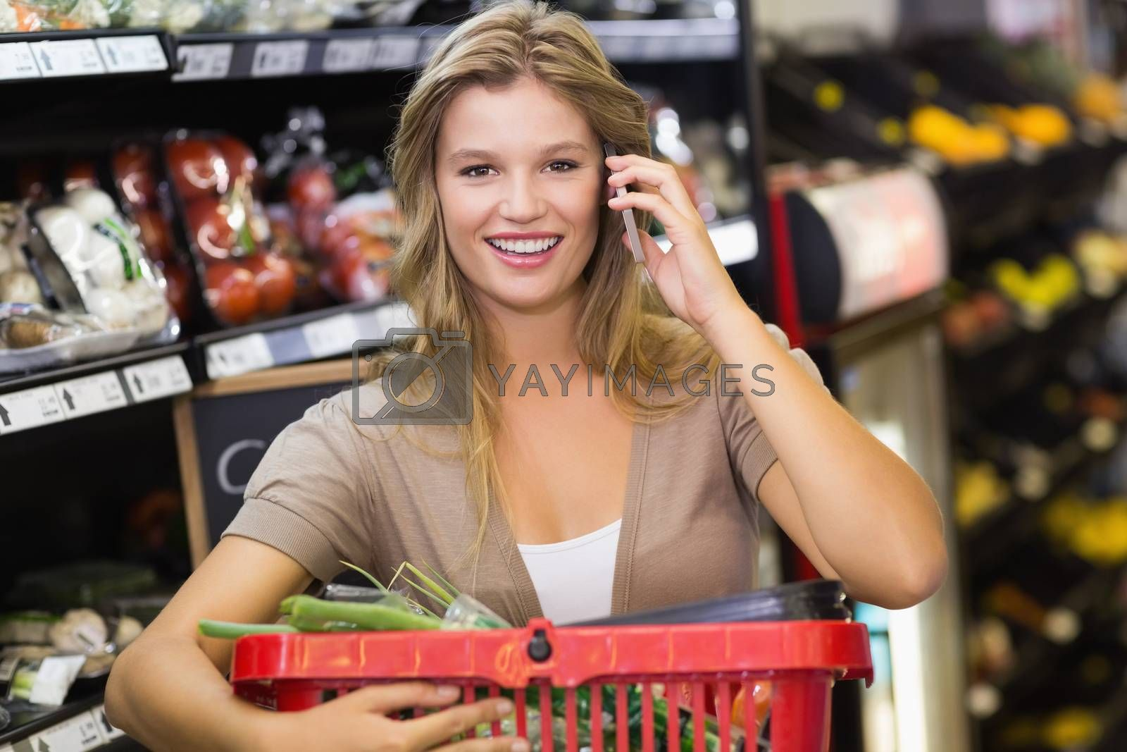 Royalty free image of Portrait of smiling blonde woman buying vegetables and phoning  by Wavebreakmedia