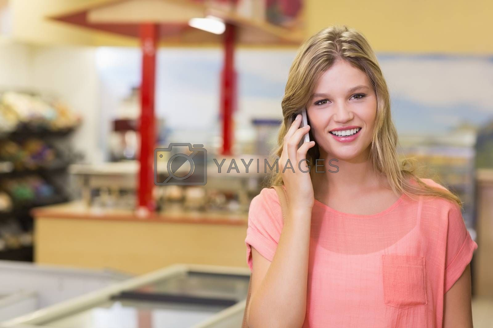 Royalty free image of Portrait of a pretty smiling blonde woman buying products and phoning  by Wavebreakmedia
