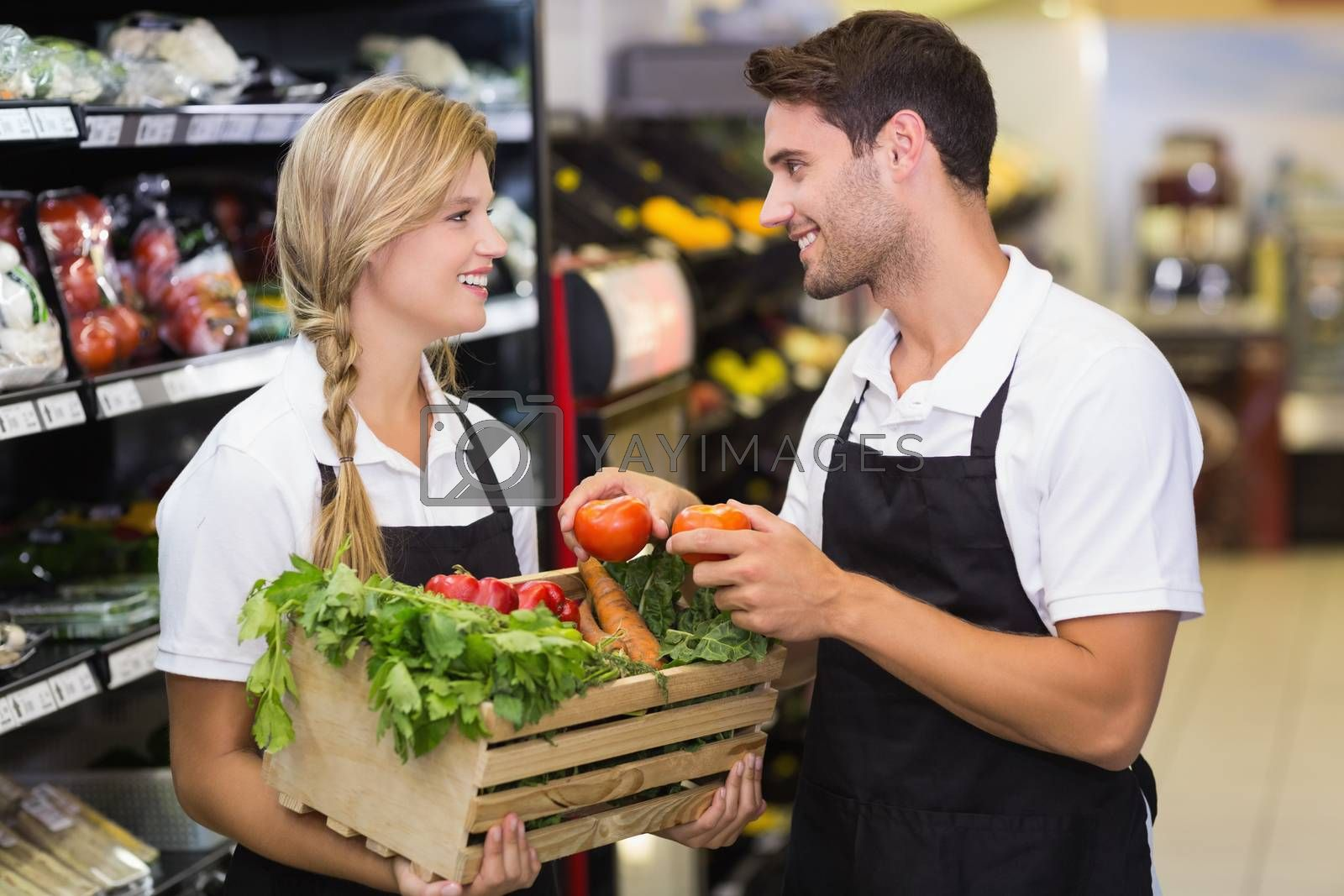 Royalty free image of Smiling colleagues holding a box with fresh vegetables  by Wavebreakmedia