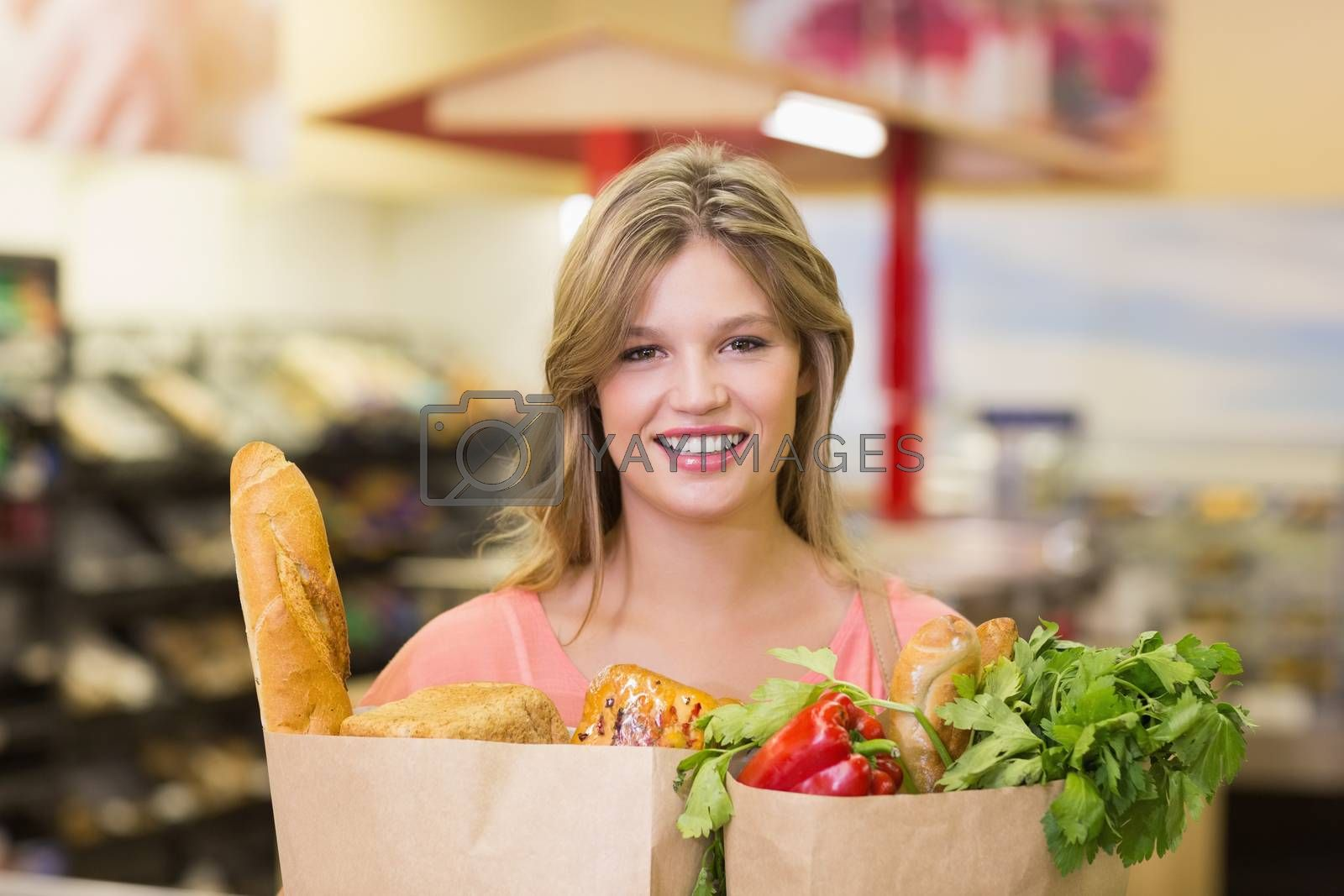 Royalty free image of Portrait of smiling pretty blonde woman buying food products by Wavebreakmedia