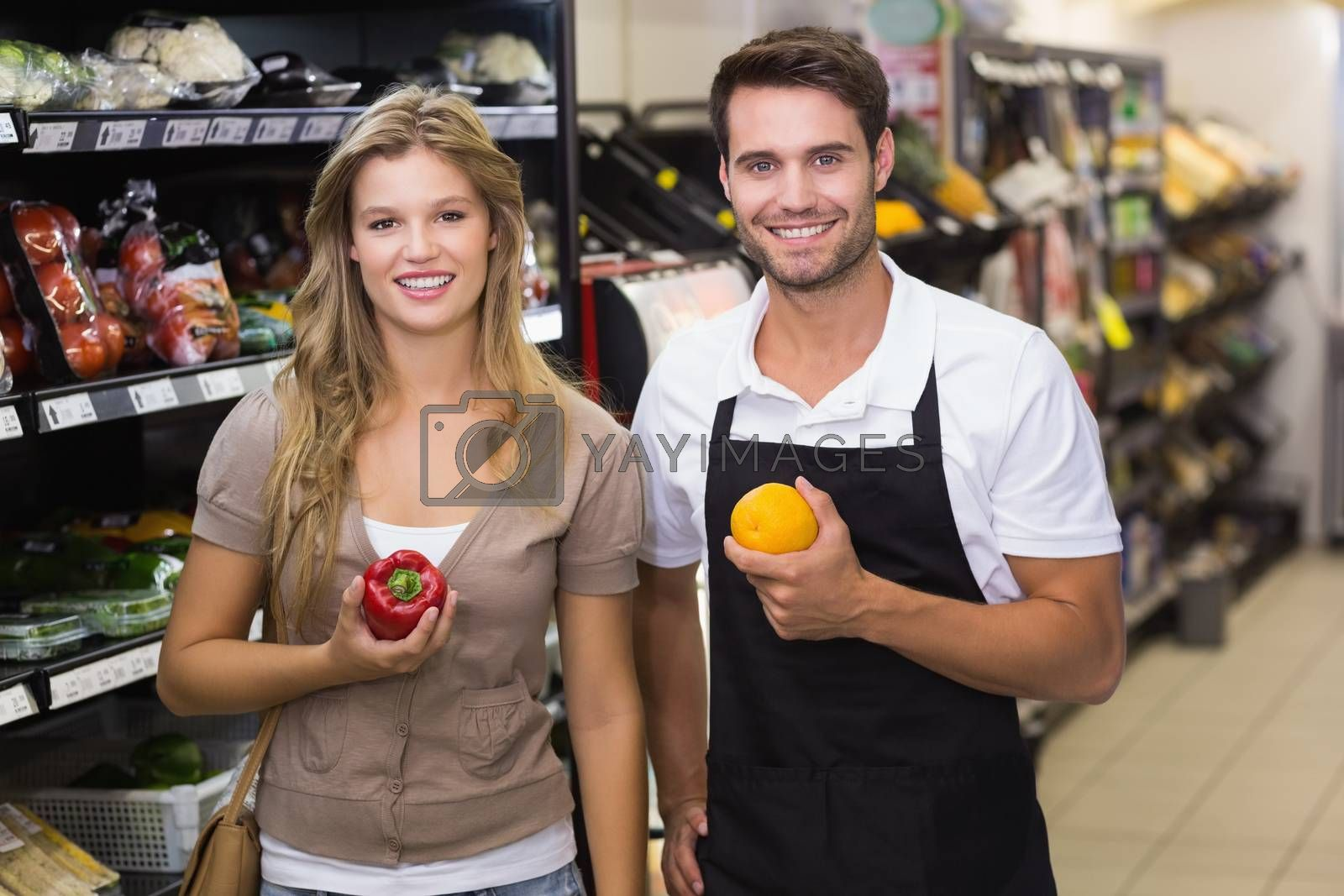 Royalty free image of Portrait of smiling pretty blonde woman buying a vegetable at seller  by Wavebreakmedia