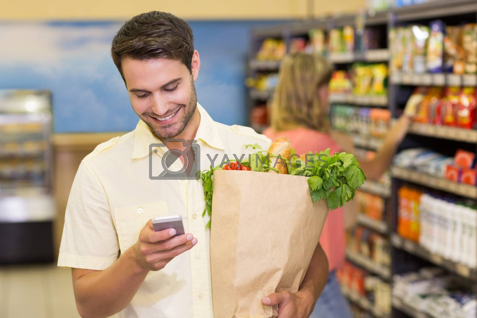 Royalty free image of Smiling handsome man buying food products and using his smartphone  by Wavebreakmedia