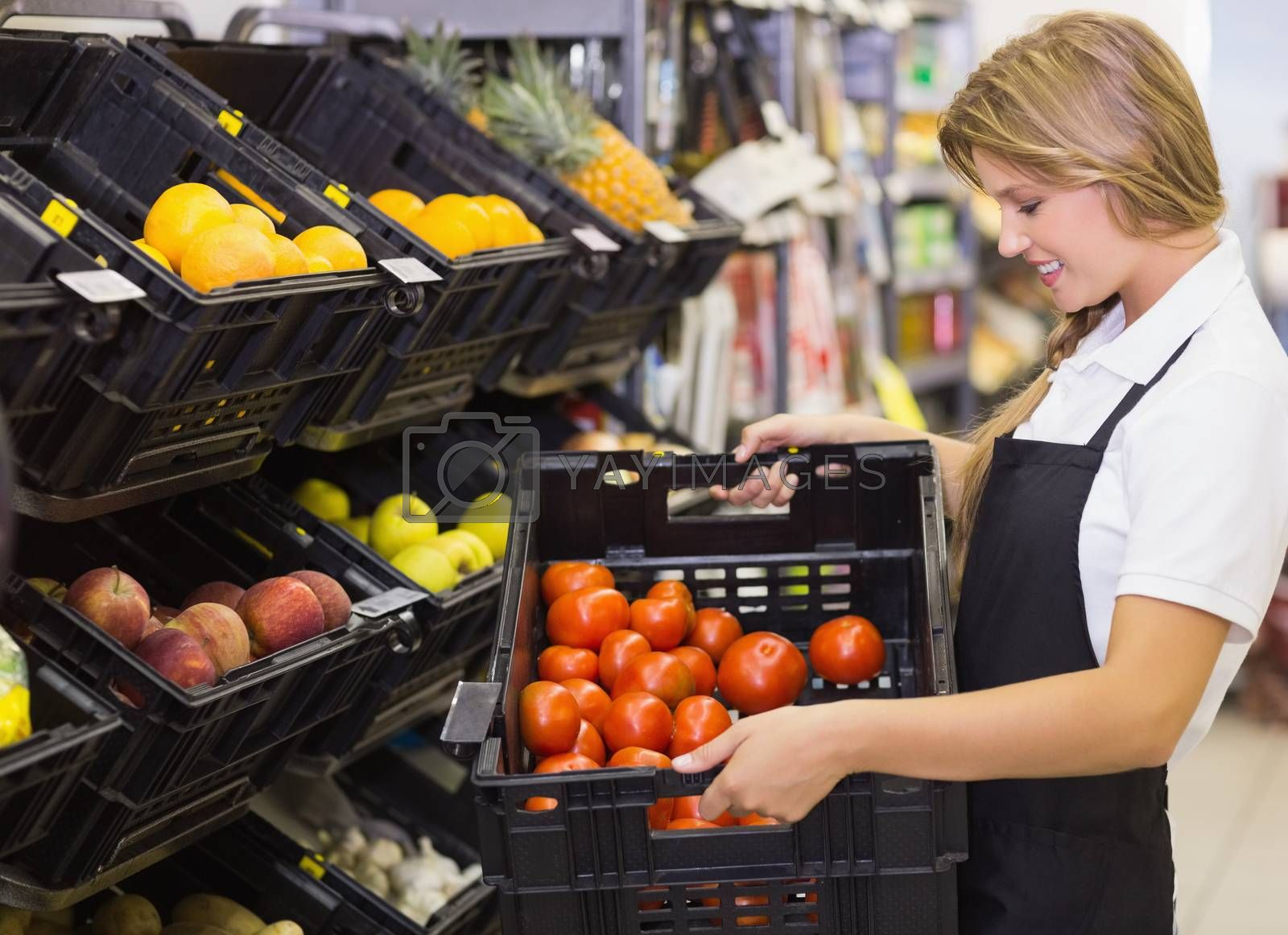 Royalty free image of Smiling staff woman holding a box with fresh vegetables by Wavebreakmedia