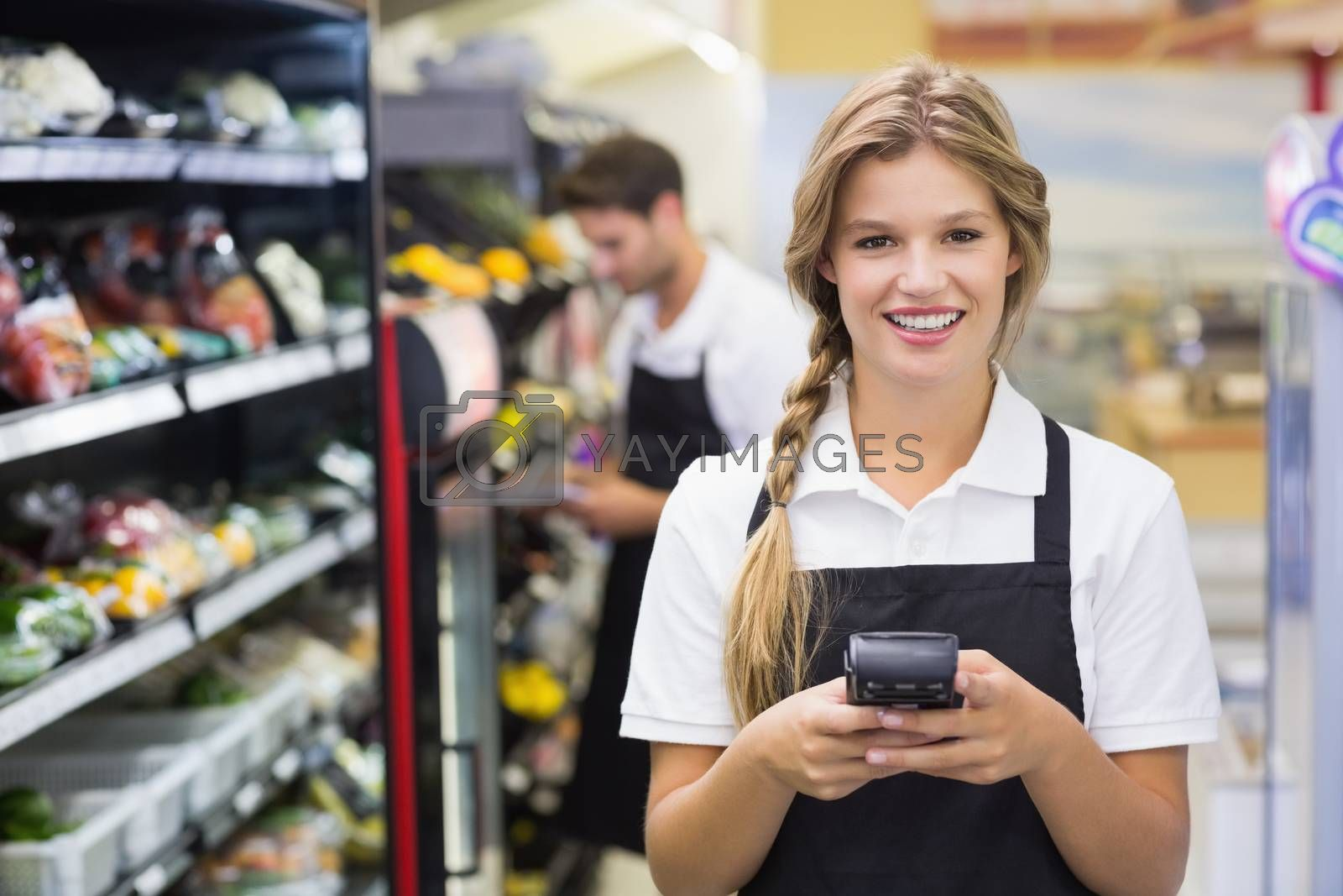Royalty free image of Portrait of smiling pretty blonde woman using handheld  by Wavebreakmedia