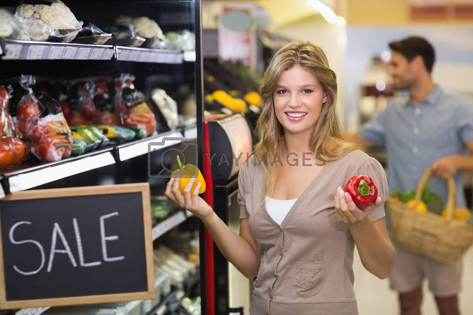Royalty free image of Portrait of a smiling pretty blonde woman buying vegetables  by Wavebreakmedia