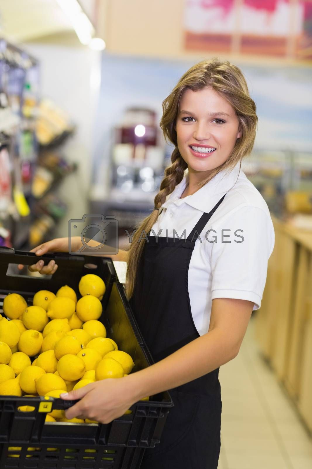 Royalty free image of Portrait of a staff woman holding a box with a fresh vegetables  by Wavebreakmedia