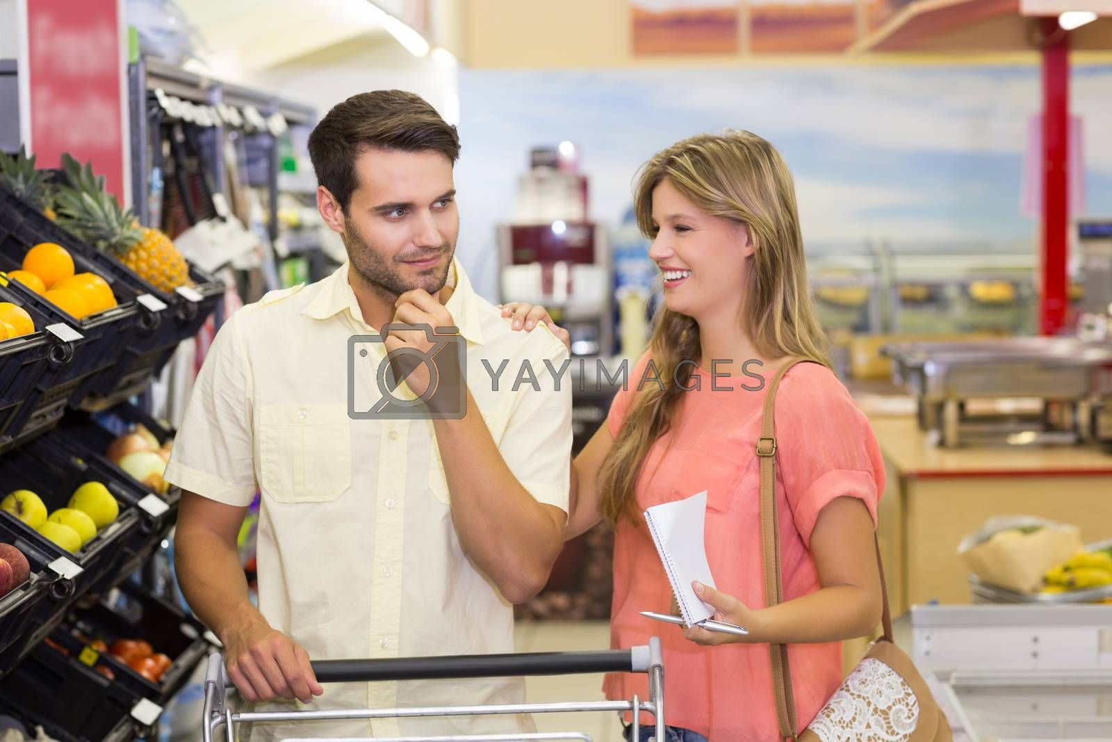Royalty free image of Smiling bright couple buying food products by Wavebreakmedia