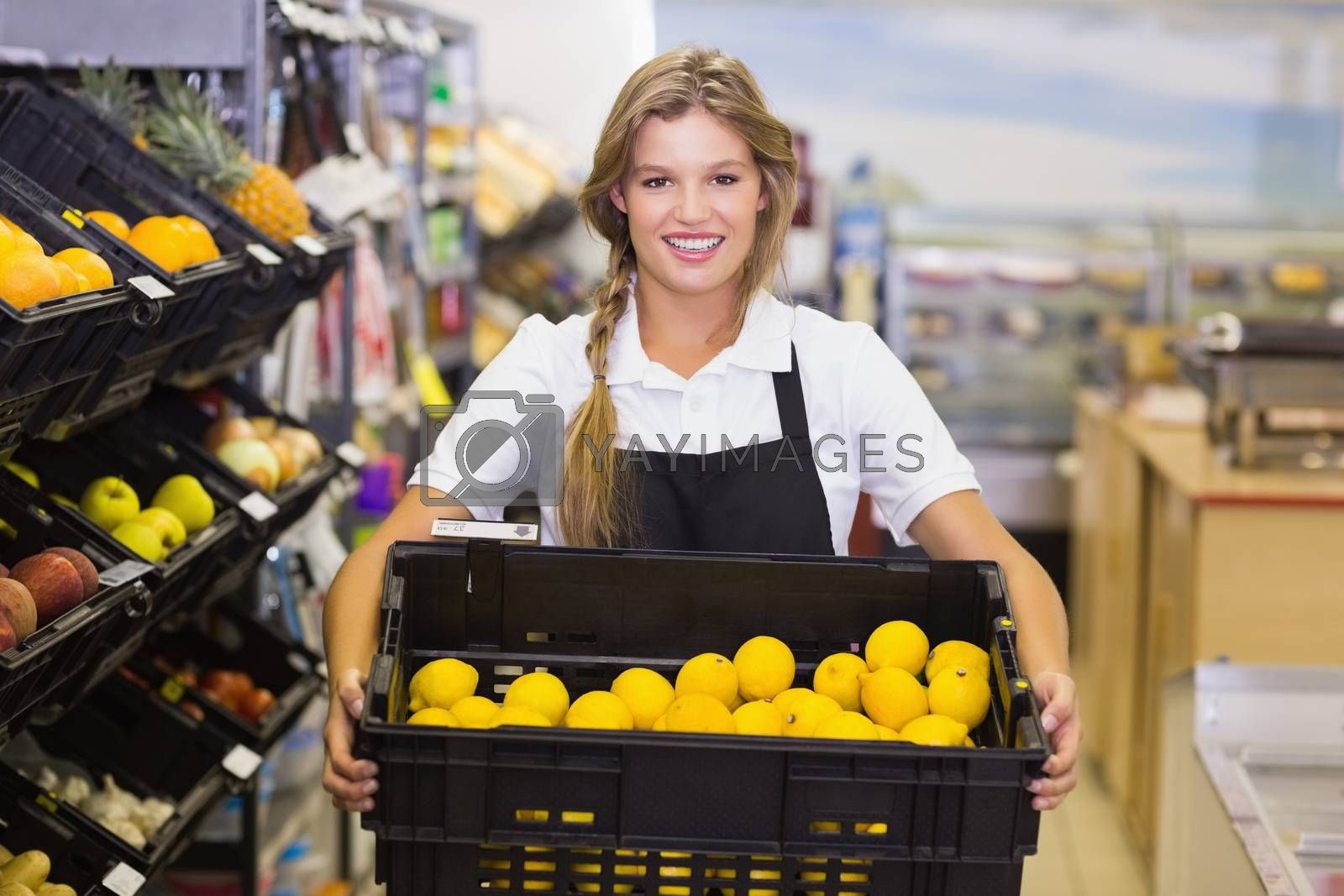 Royalty free image of Portrait of a staff woman holding a box with fresh vegetables  by Wavebreakmedia