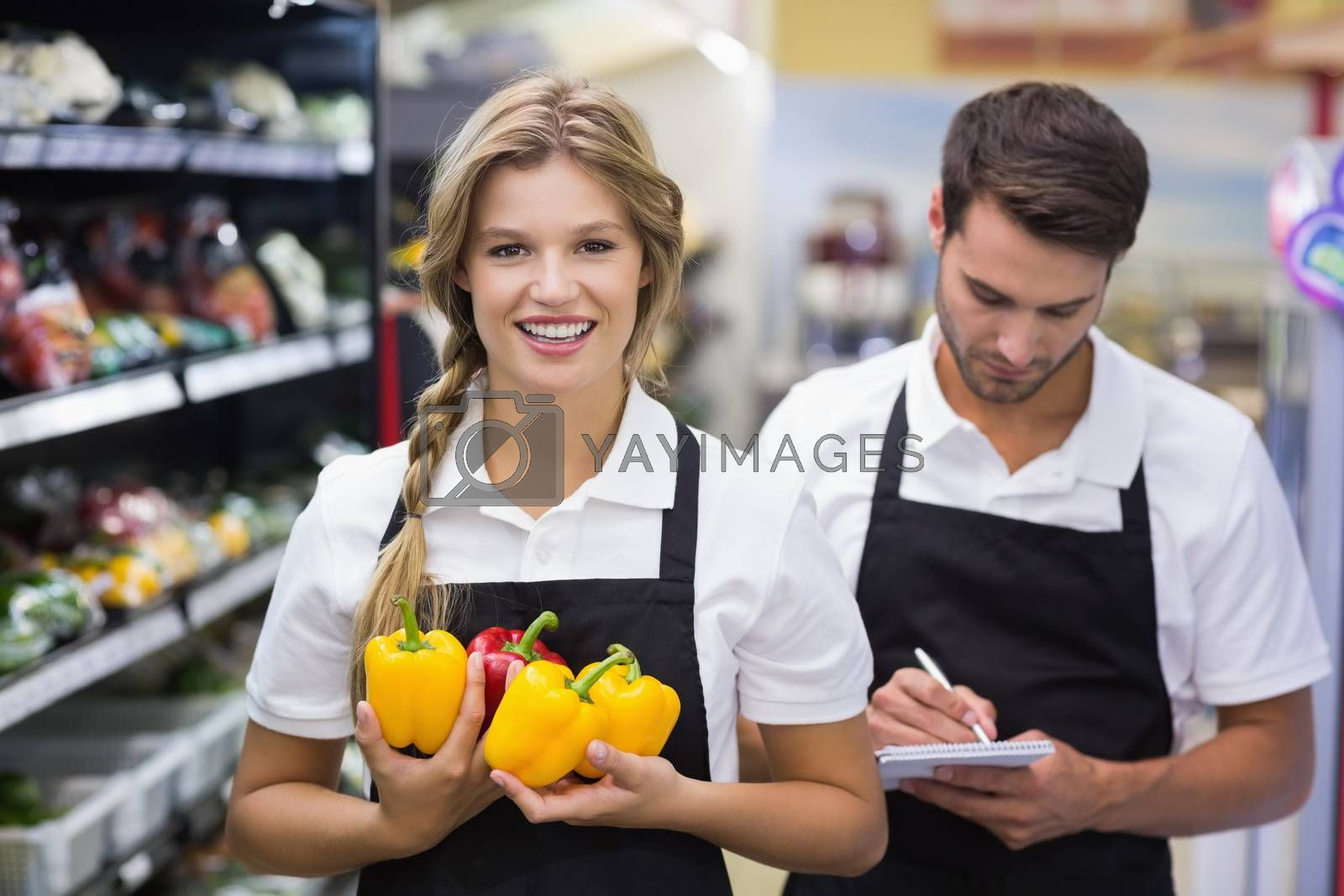 Royalty free image of Portrait of smiling blonde woman having vegetables and writing on notepad  by Wavebreakmedia