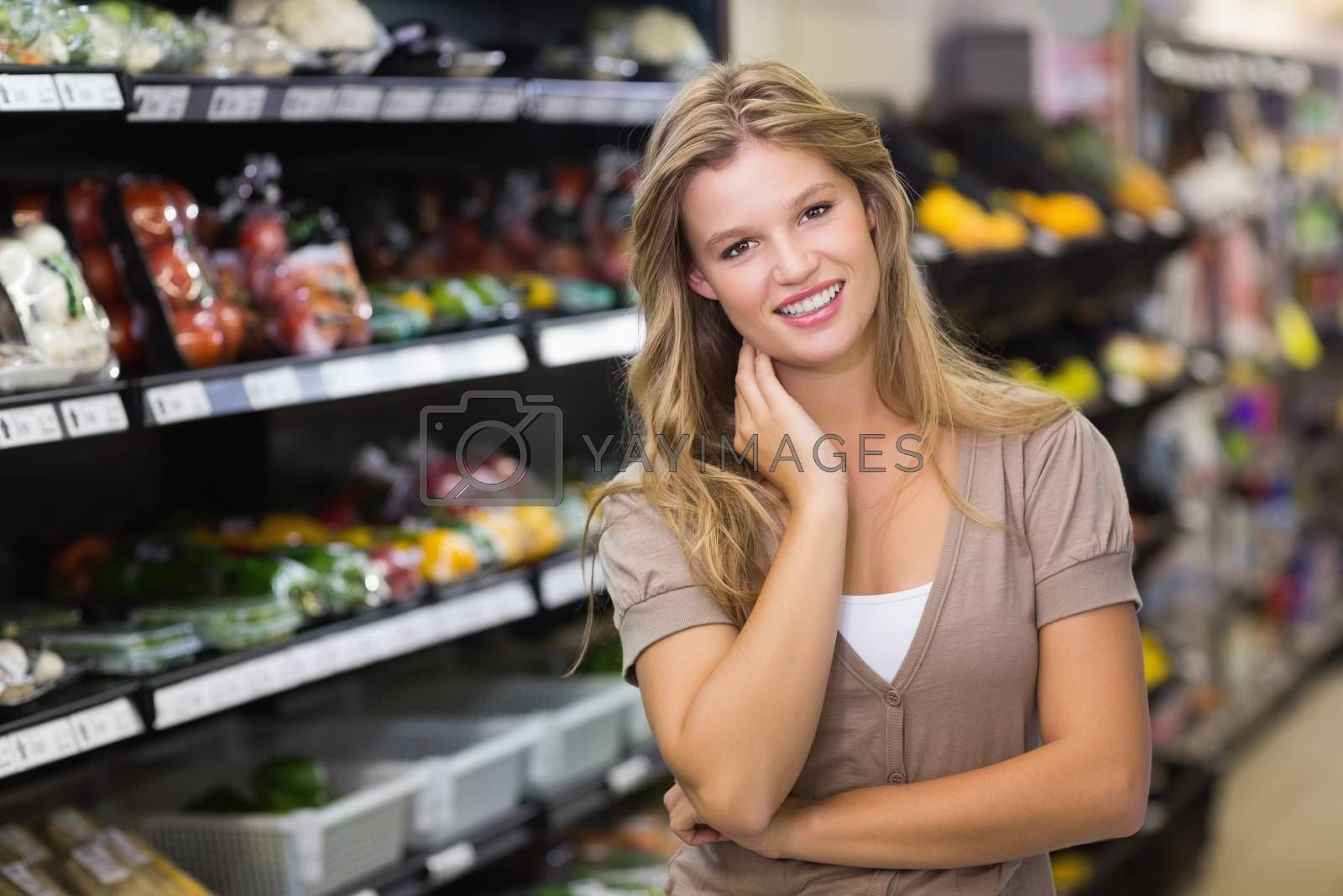 Royalty free image of Portrait of a pretty blonde woman with hand on face  by Wavebreakmedia