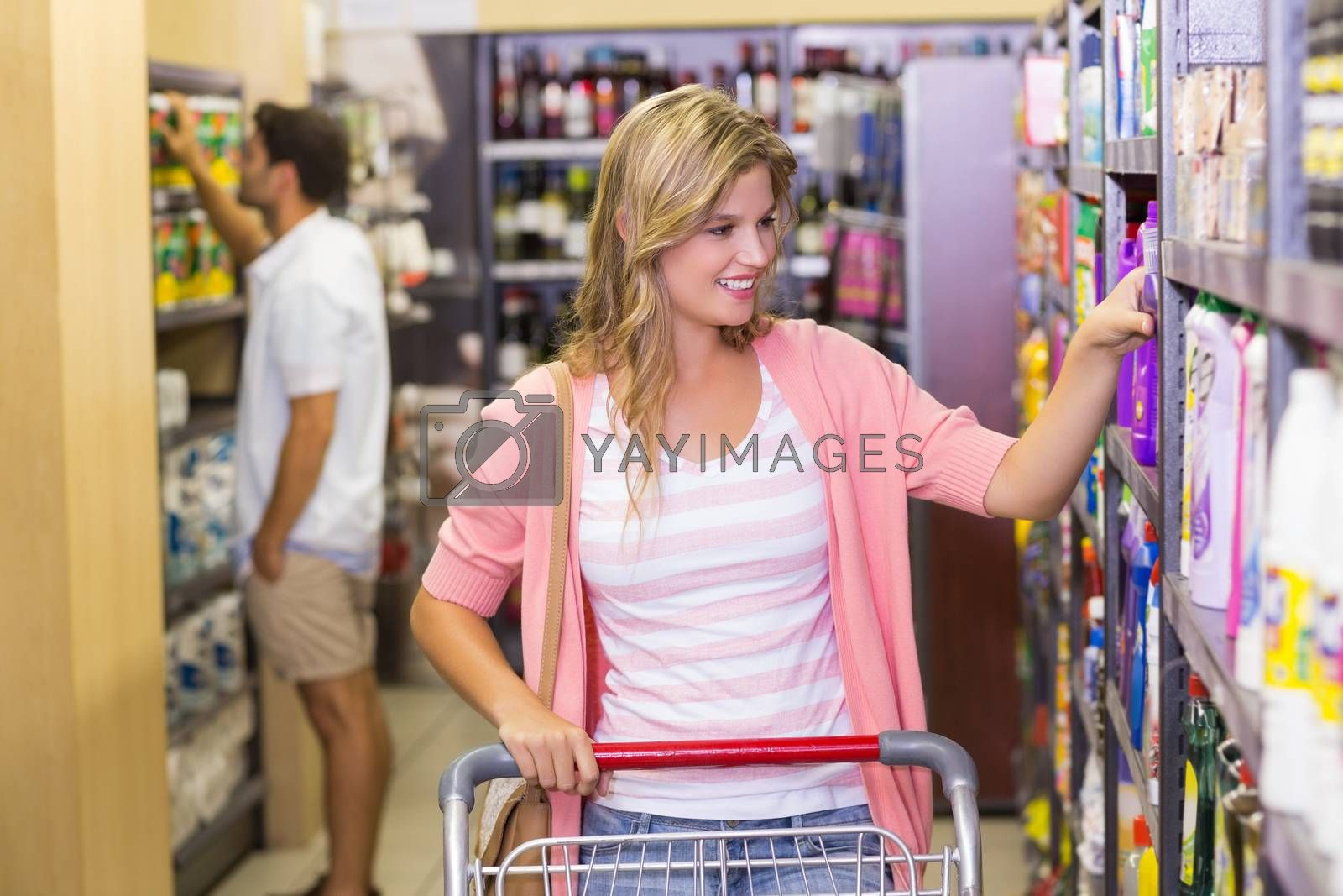 Royalty free image of Smiling blonde woman taking a product on shelf  by Wavebreakmedia
