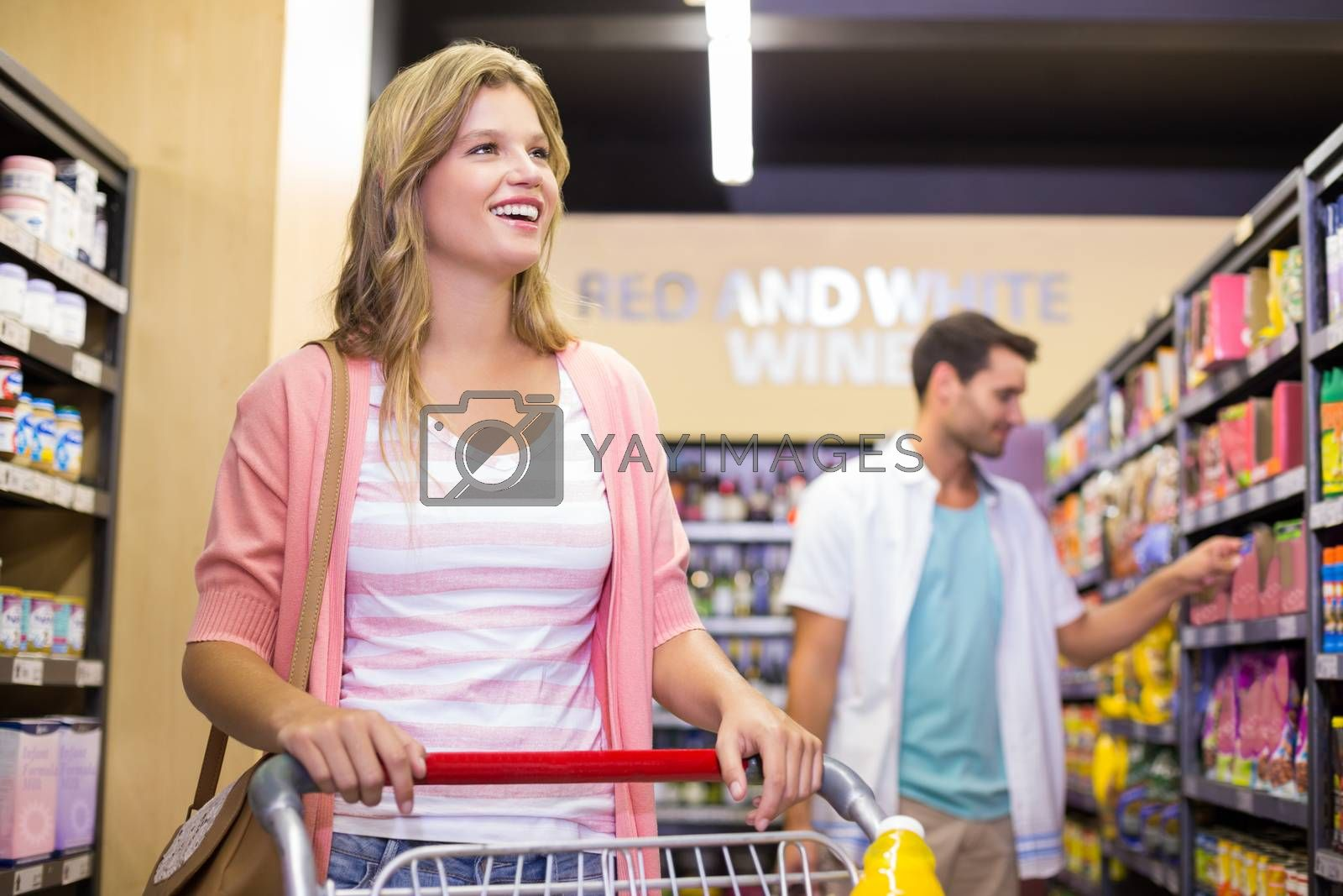 Royalty free image of Smiling pretty woman buying a products  by Wavebreakmedia
