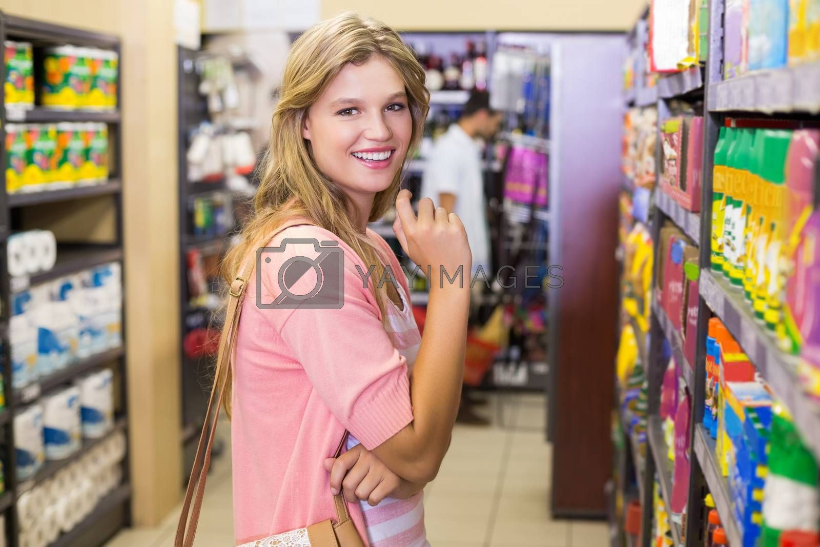 Royalty free image of Portrait of a smiling young woman buying a products  by Wavebreakmedia