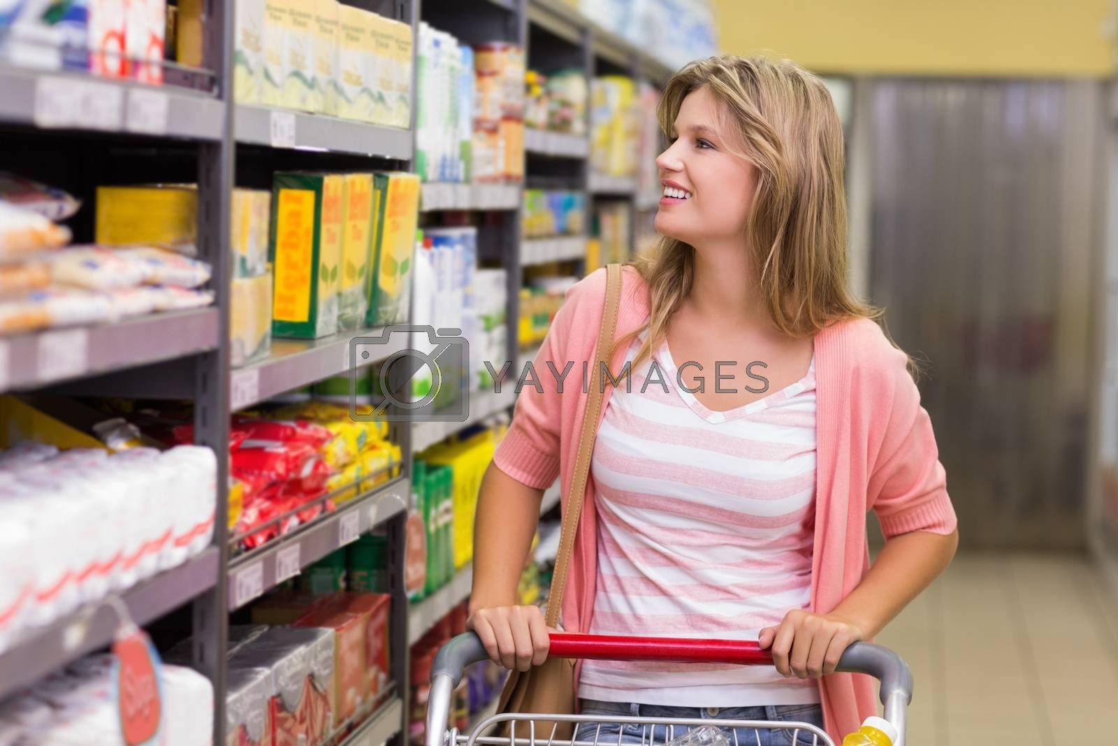 Royalty free image of Smiling pretty blonde woman looking at shelf and buying a products  by Wavebreakmedia