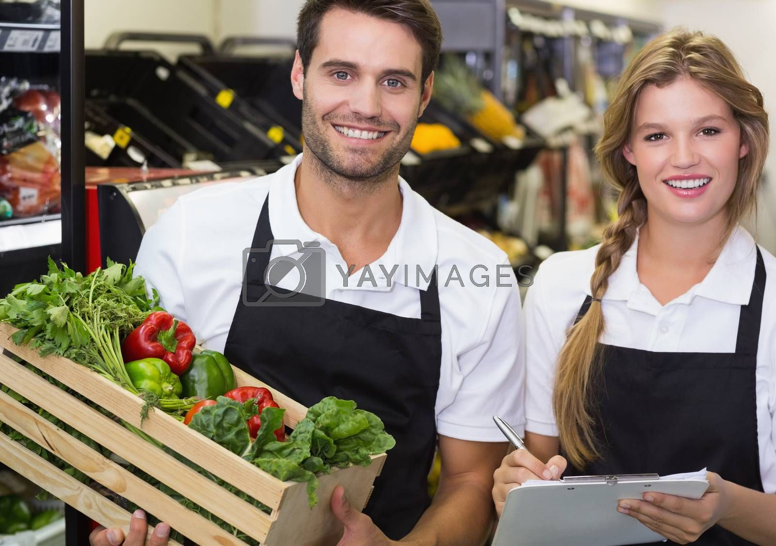 Royalty free image of Portrait of two colleagues holding a box with fresh vegetables and writing on notepad  by Wavebreakmedia