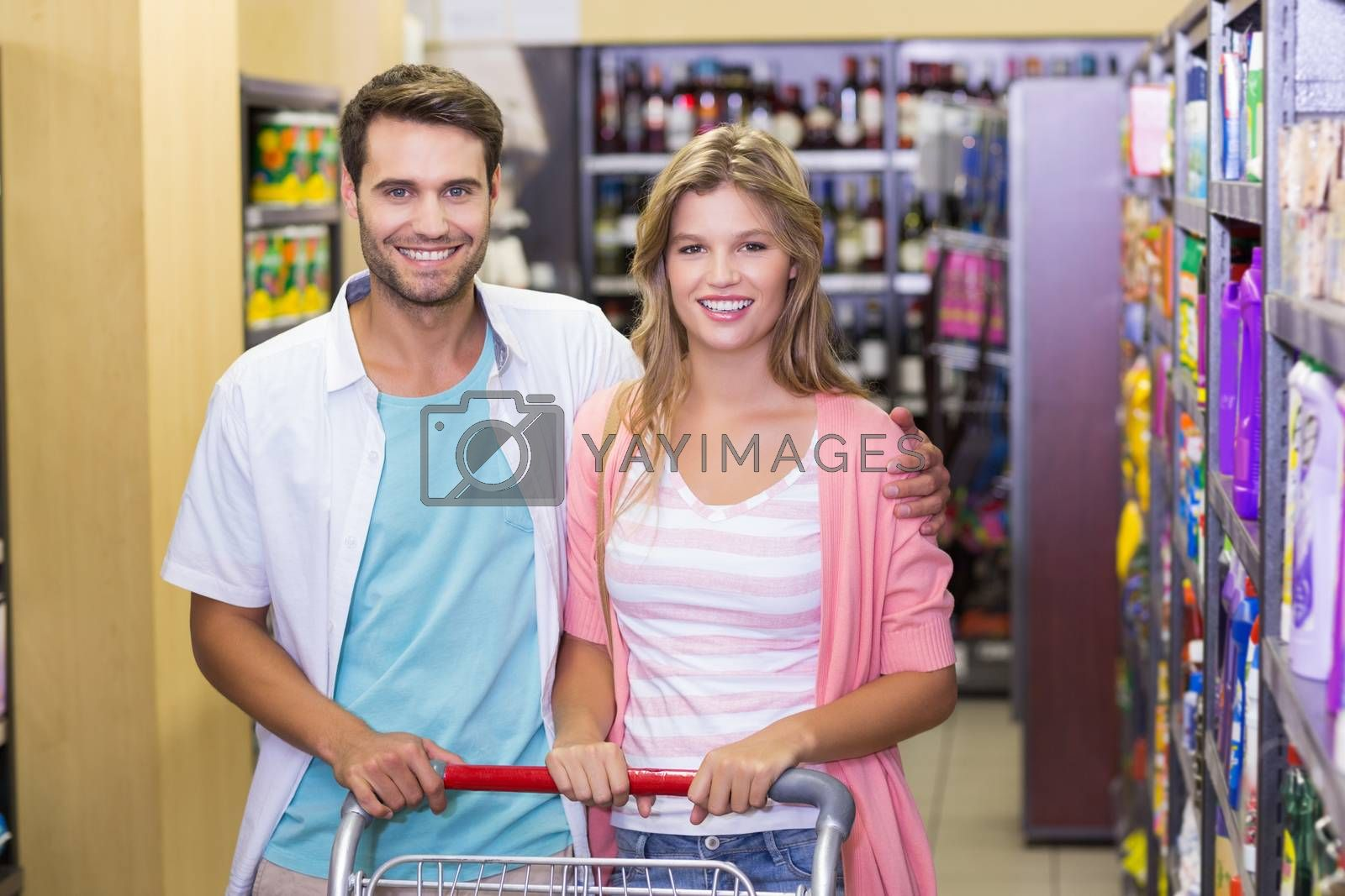 Royalty free image of Portrait of smiling bright couple with arm around  by Wavebreakmedia